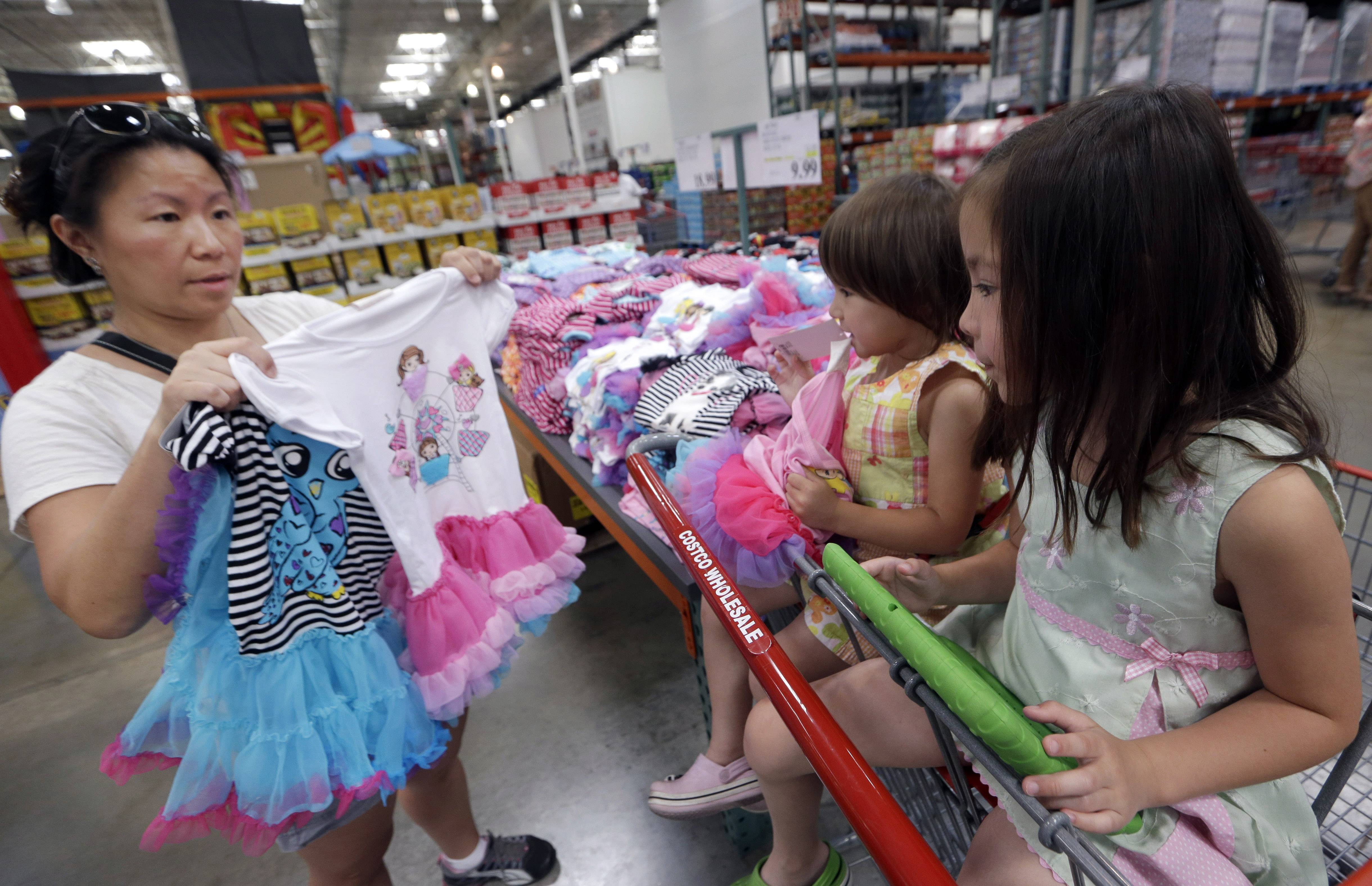Carry Johnson, left, shows dresses to her daughters Zoey, 3, center, and Payton while they shop at a Costco in Plano, Texas. Confidence among U.S. consumers soared in July to the highest level in almost seven years as Americans grew more upbeat about the labor market and the outlook for the economy.
