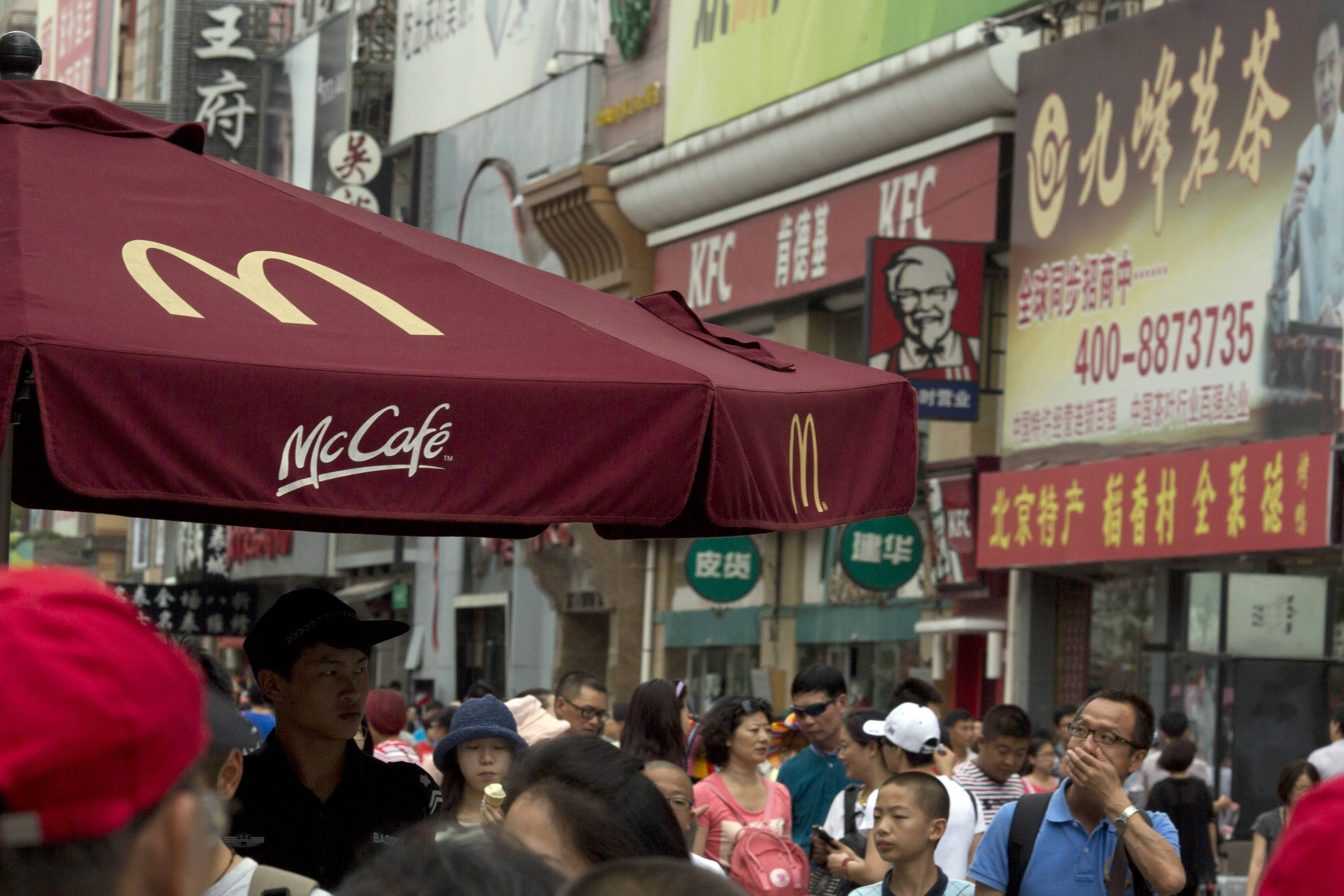 A man wipes his mouth near logos for McDonald's and KFC restaurants in Beijing Tuesday. McDonald's in Japan is increasing its checks on chicken from suppliers in China and Thailand after allegations a Chinese supplier sold expired chicken. It says the scare will hurt its earnings.