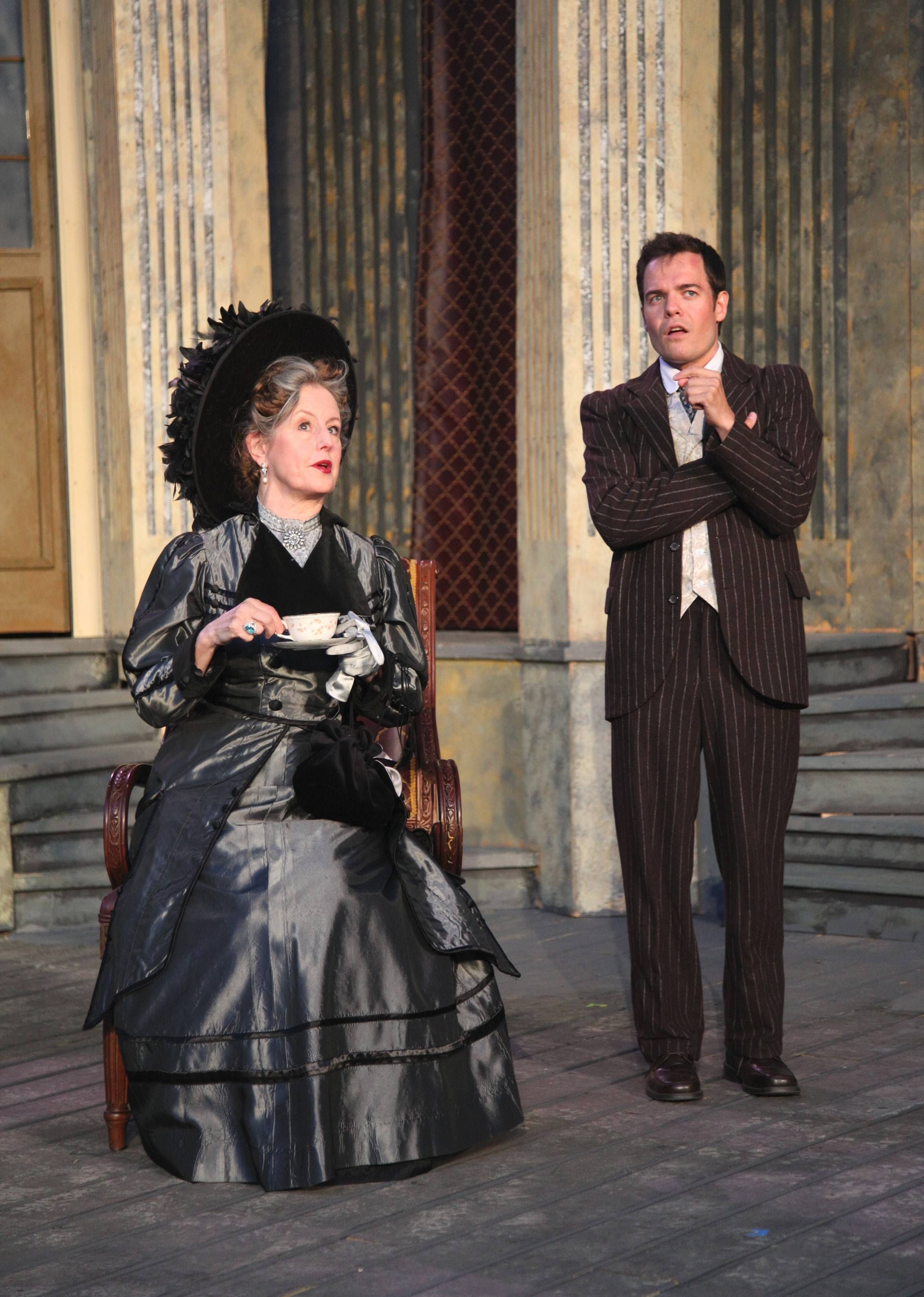 "Algernon (Jude Willis), right, lies about an ill relative to get out of a dinner party hosted by Lady Bracknell (Belinda Bremner) in Oak Park Festival Theatre's outdoor production of Oscar Wilde's 1895 comedy ""The Importance of Being Earnest."""