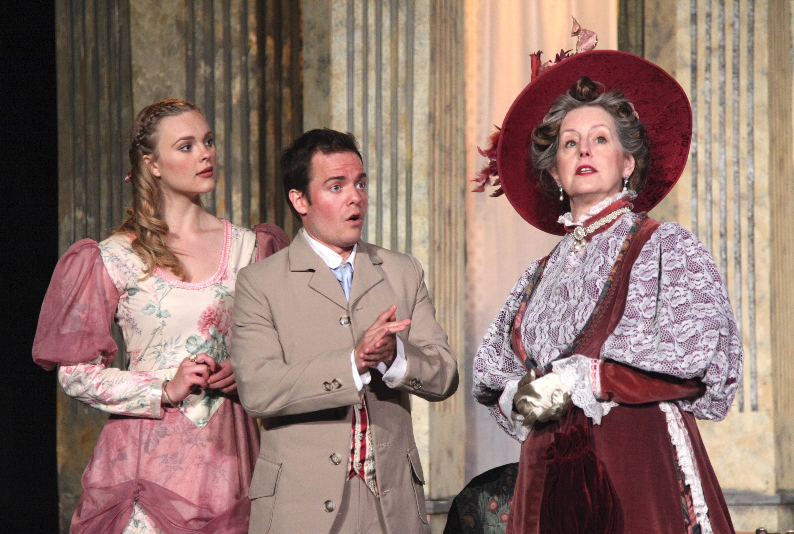 "Cecily (Brooke Hebert) and Algernon (Jude Willis) share the news of their engagement to a very skeptical Lady Bracknell (Belinda Bremner) in Oak Park Festival Theatre's outdoor production of Oscar Wilde's 1895 comedy ""The Importance of Being Earnest."""