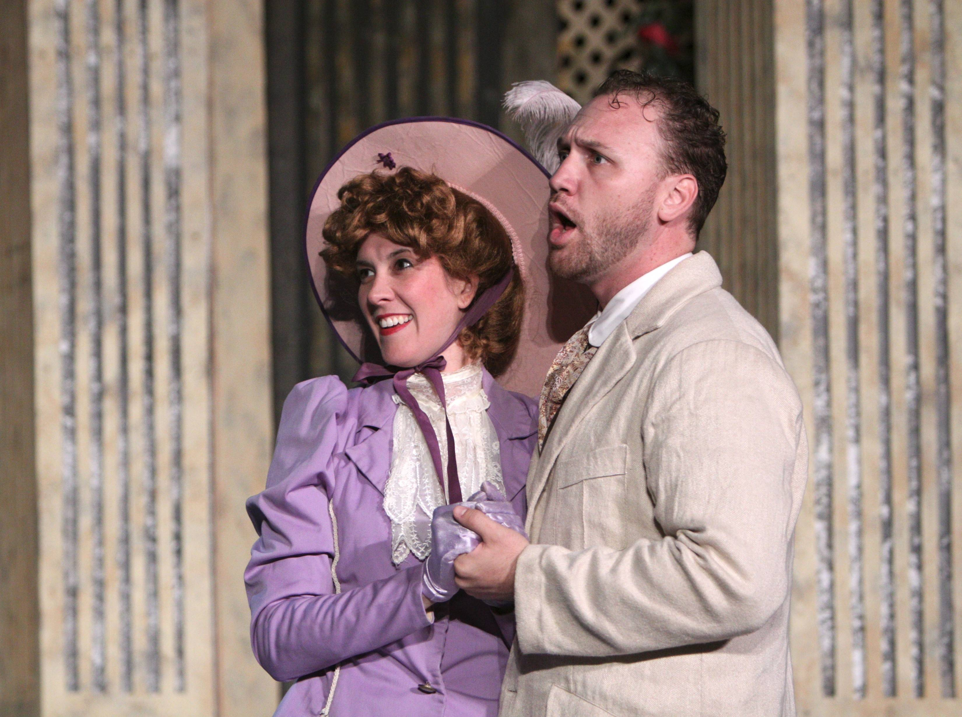 "Gwendolyn (Elise Kauzlaric) and Jack (John Crosthwaite) gleefully await an admission from the tutor Miss Prism in Oak Park Festival Theatre's outdoor production of Oscar Wilde's 1895 comedy ""The Importance of Being Earnest"" in Austin Gardens."