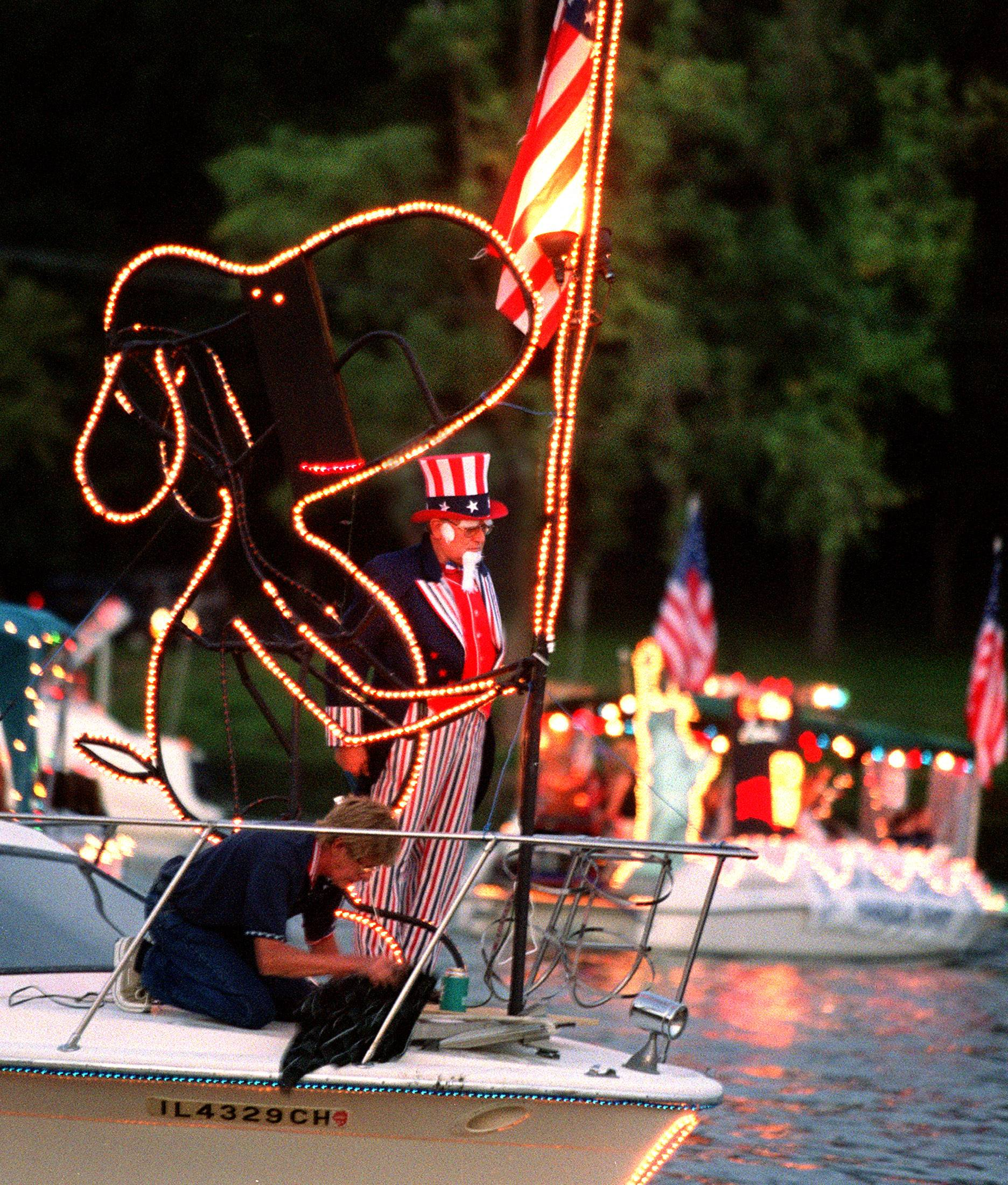 A boat sporting Uncle Sam and Snoopy during venetian boat night on the Fox River in Algonquin.
