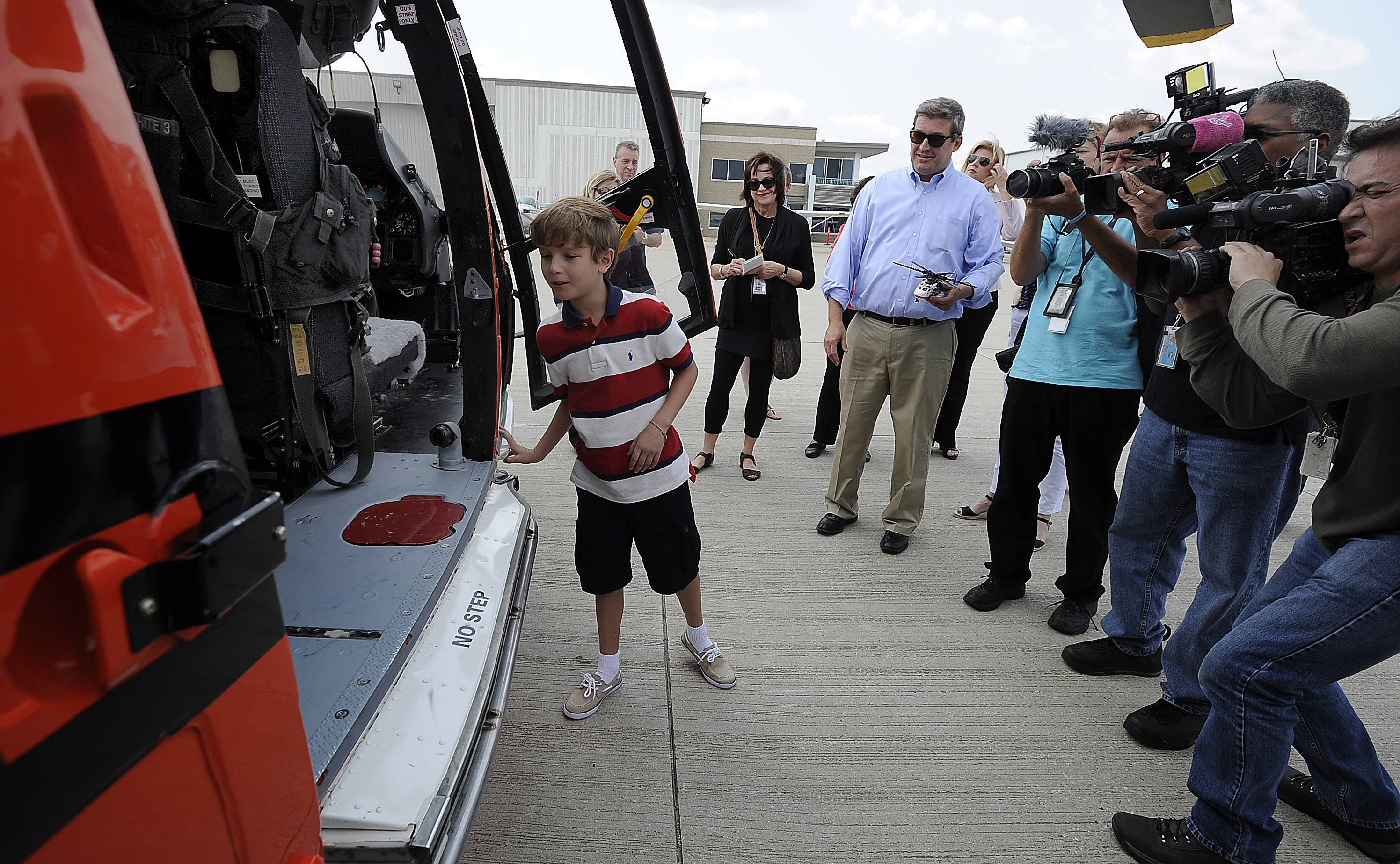 Tommy Alter peers inside the Dolphin helicopter, the one that was used to rescue him, his aunt and cousin July 11 in Door County, Wisconsin.