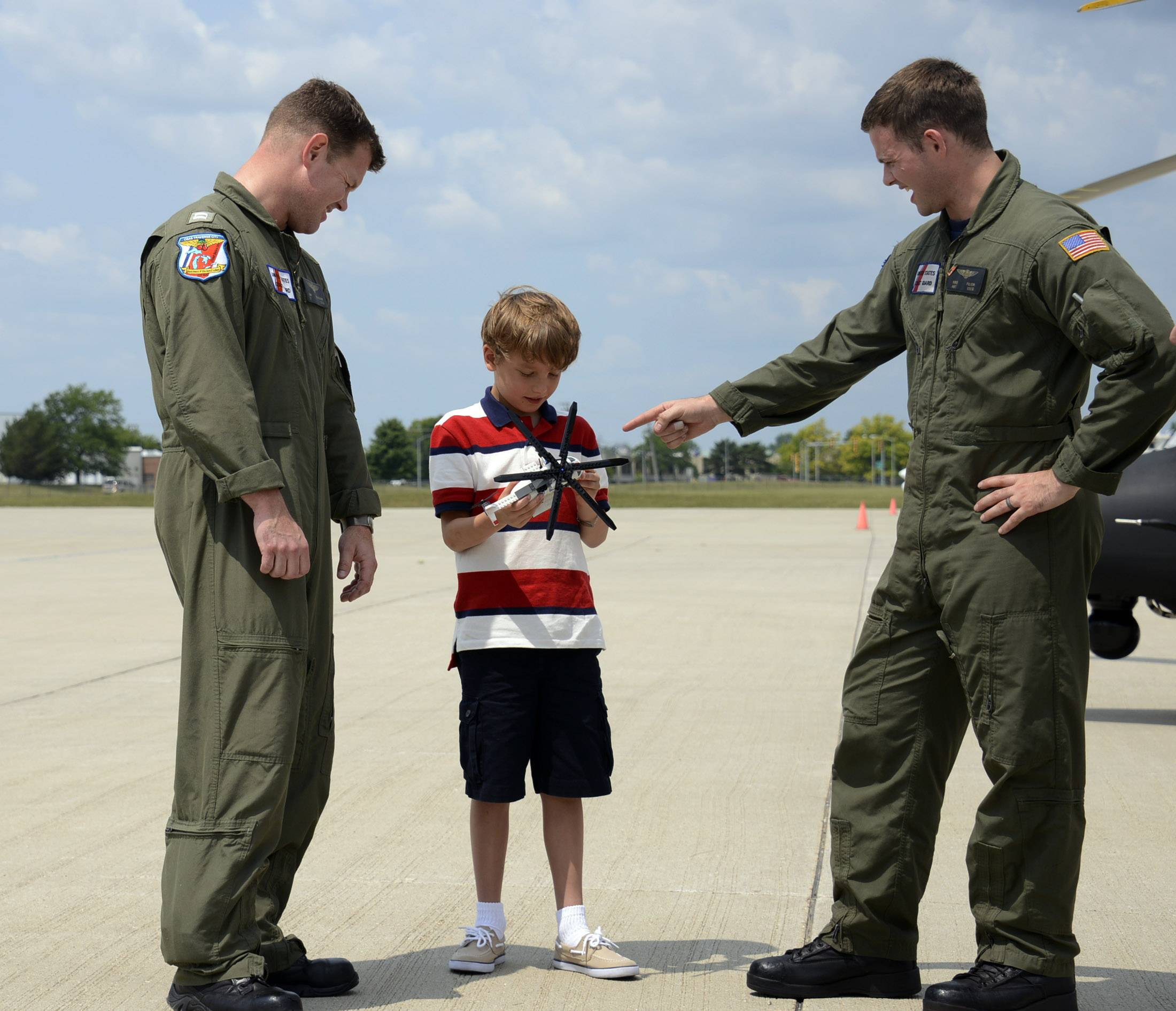Tommy Alter, 9, of Highland Park is joined by Coast Guard Lt. Dan Schrader and Kris Filion, the flight mechanic, at the Wheeling airport Tuesday.