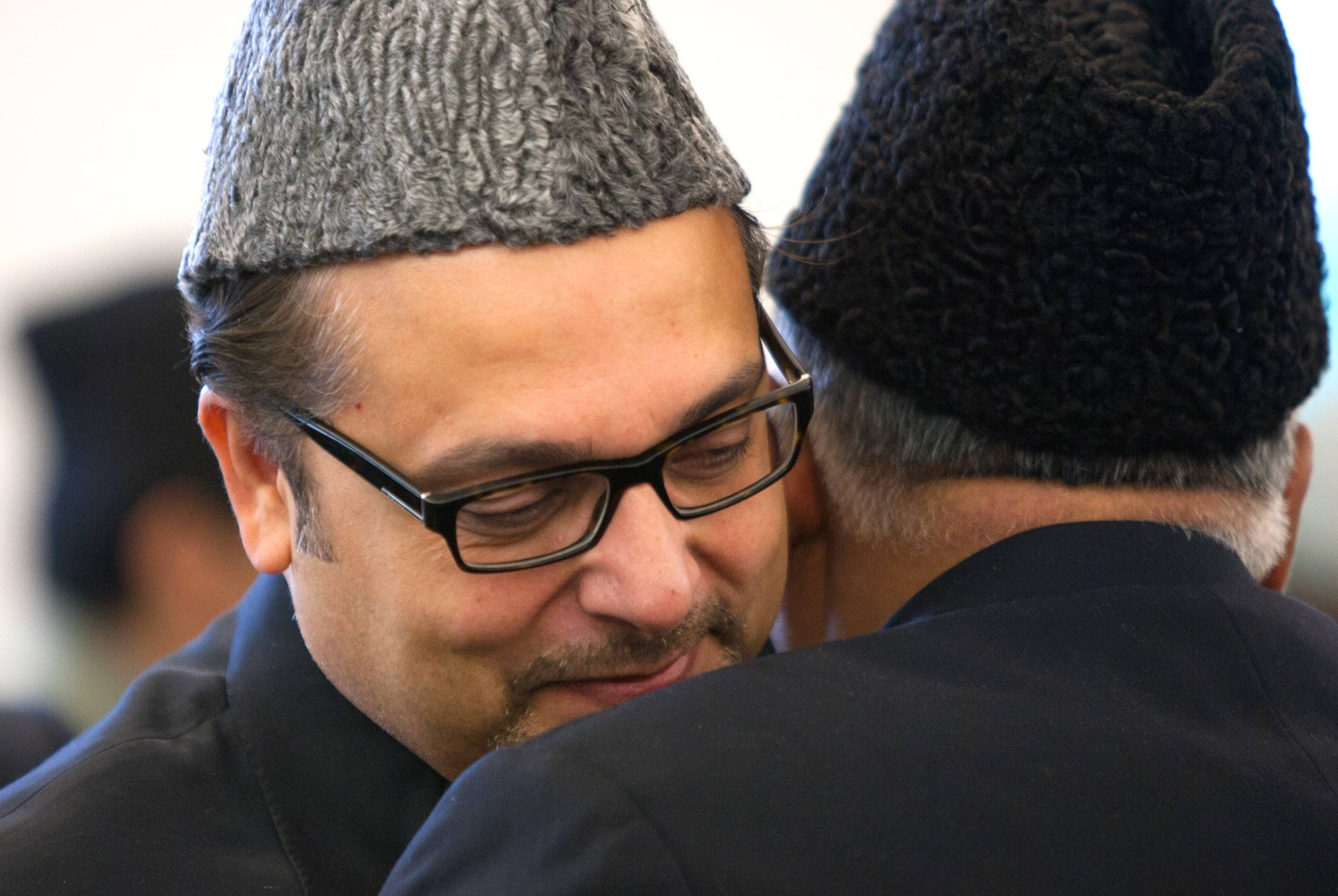 Haris Ahmed, director of public affairs of the Chicago West Chapter, greets a fellow worshipper as the Ahmadiyya Muslim Community celebrates the end of Ramadan.