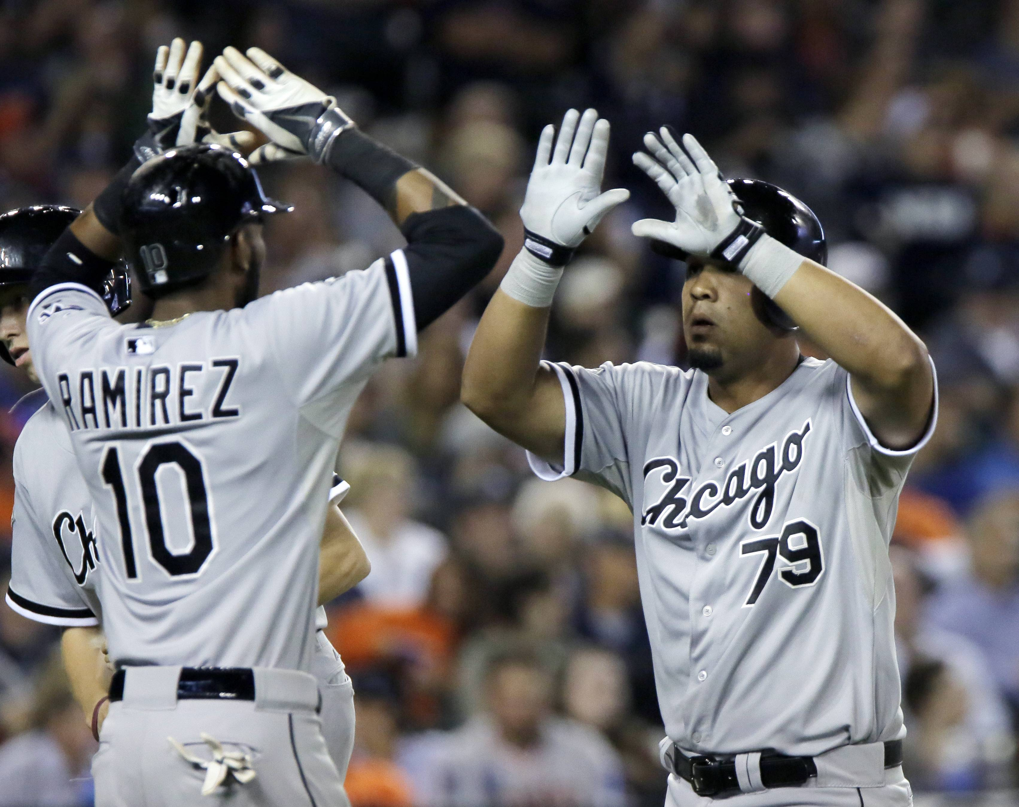 Chicago White Sox's Jose Abreu is congratulated by Alexei Ramirez after hitting a two run home run off of Detroit Tigers pitcher Joakim Soria during the seventh inning of a baseball game Tuesday, July 29, 2014, in Detroit.