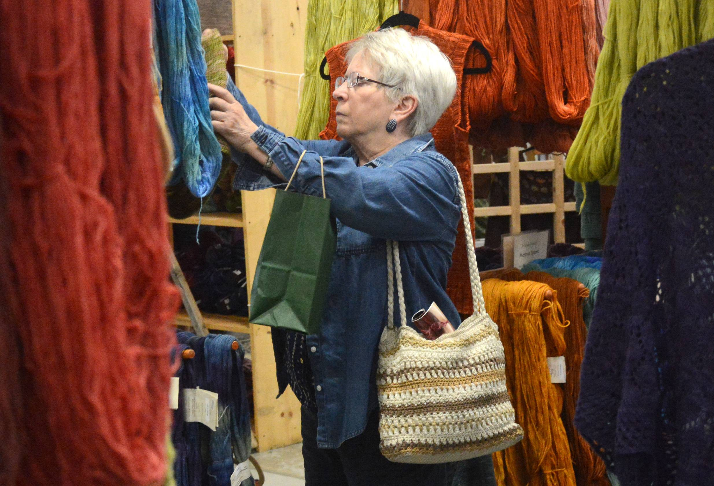 Barbara Lies of Madison, Wisconsin, looks through rows of yarn at last year's Midwest Fiber and Folk Art Fair in Grayslake. This year's fair will be from 10 a.m. to 6 p.m. Friday, Aug. 1, and Saturday, Aug. 2, and 10 a.m. to 4 p.m. Sunday, Aug. 3, at the Lake County Fairgrounds.