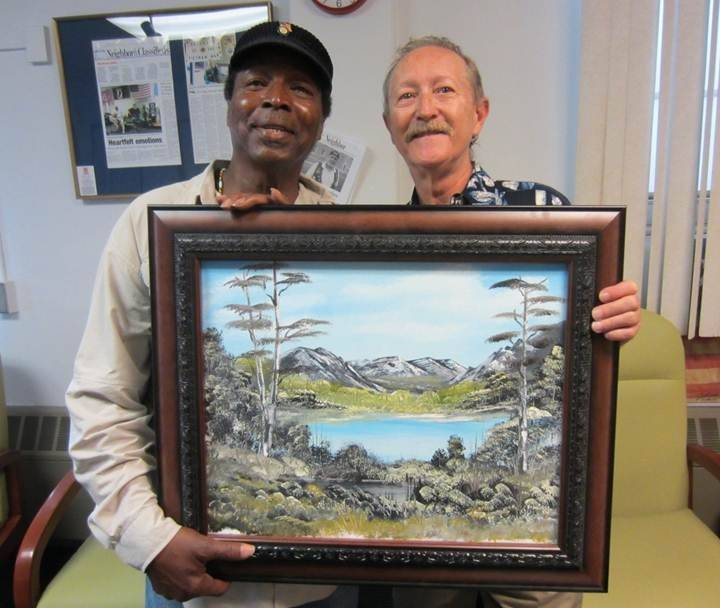 Vietnam veteran Johnnie Johnson, left, displays the oil painting fellow Vietnam veteran Rick Beauvais, right, painted and presented to him earlier this year. Both are members of the Friday Expressive Arts Therapy group at Lovell FHCC, which recently received more than $2,000 worth of oil paints and other art supplies from USVAP.
