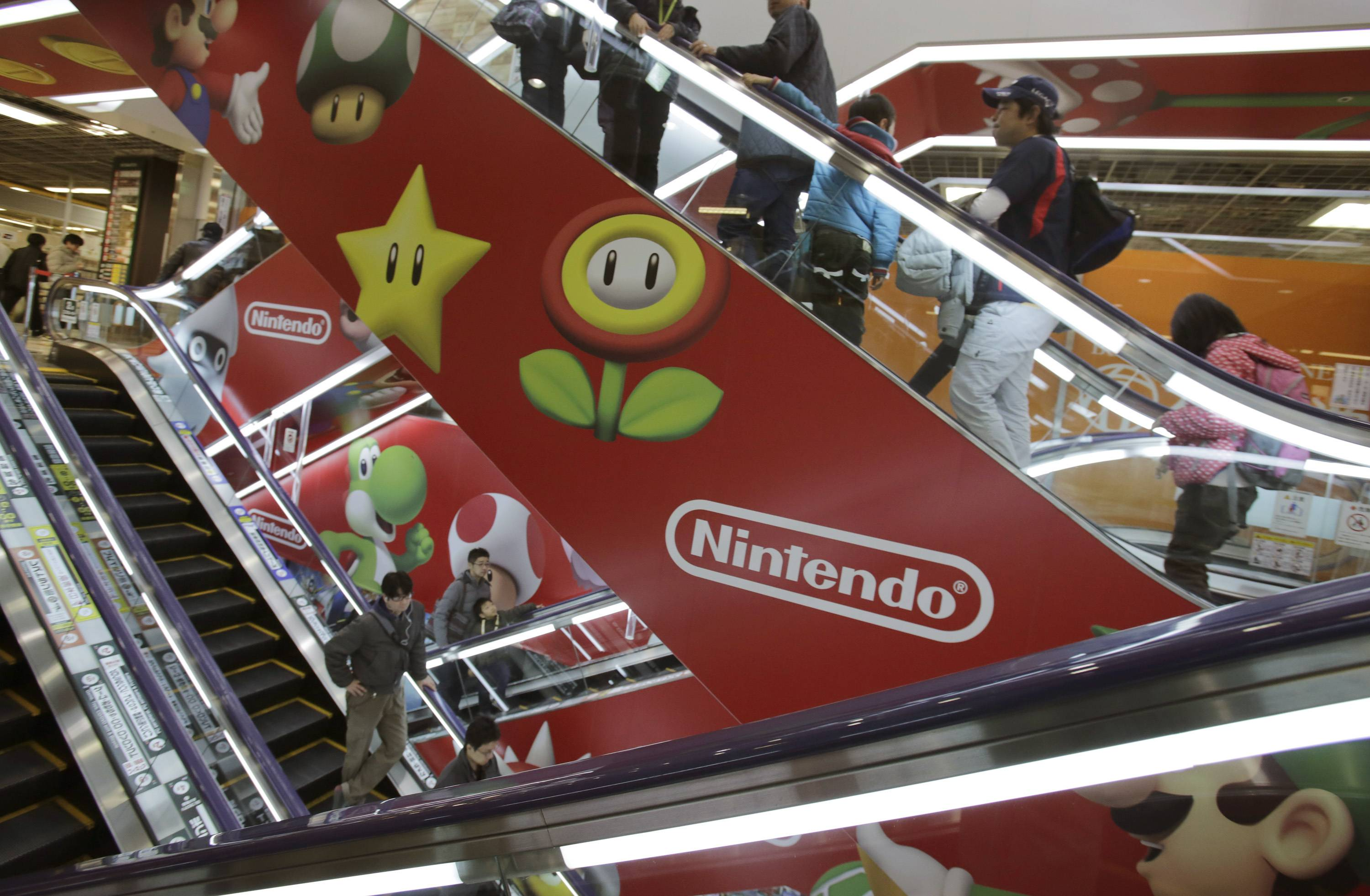 Bloomberg News Shoppers take escalators painted with the logos of Nintendo and Super Mario characters at an electronics store in Tokyo. Nintendo Co. sank to a worse-than-expected loss for the fiscal first quarter on lagging Wii U and 3DS video-game machine sales.