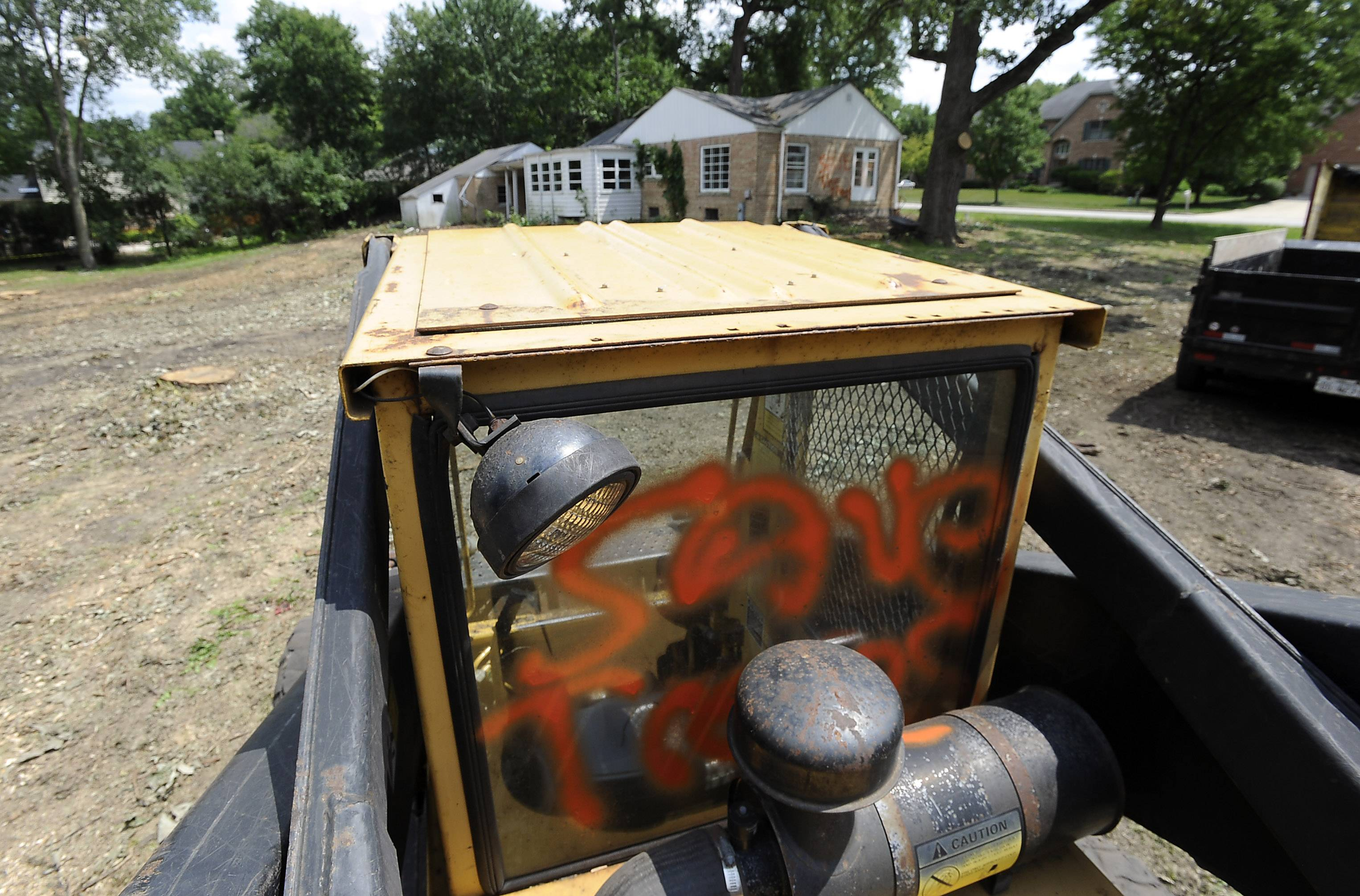 Equipment on a construction site in Rolling Meadows where trees were cut down last week was defaced with messages calling for the developer to save the trees.