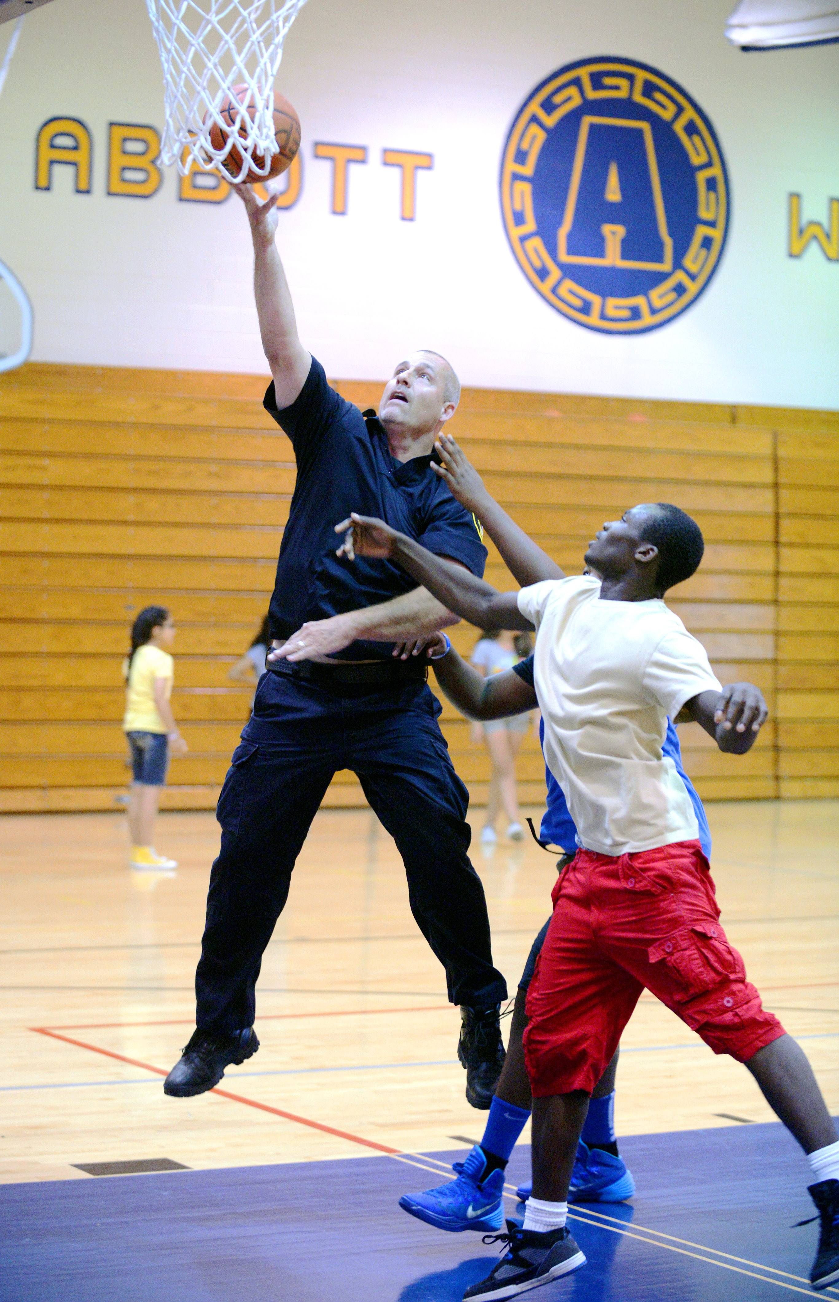 Elgin police officer Mike Kata plays basketball with Aris Johnson, 14 (obscured), and Darius Hill, 15, on Tuesday night during the Elgin Police Department's Kids United program at Abbott Middle School. This is the first year Darius and Aris have been in the program. Kata, who has been with the police department for 11 years, will be the new school resource officer at Abbott Middle School this fall.