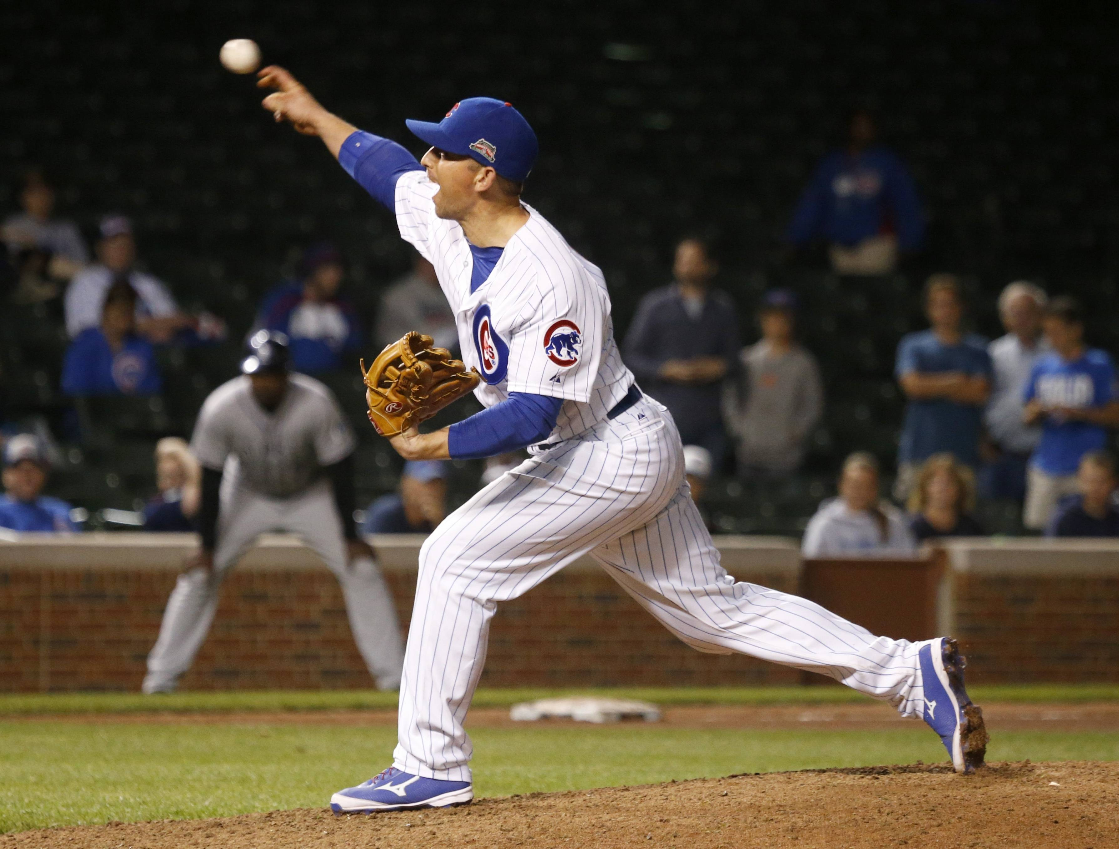 Chicago Cubs back up catcher John Baker, pitches in relief during the 16th inning of a baseball game against the Colorado Rockies, early Wednesday, July 30, 2014, in Chicago. Baker score the winning run off a sacrifice fly by Starlin Castro, in the bottom of the inning giving the Cubs' a 4-3 victory. (AP Photo/Charles Rex Arbogast)