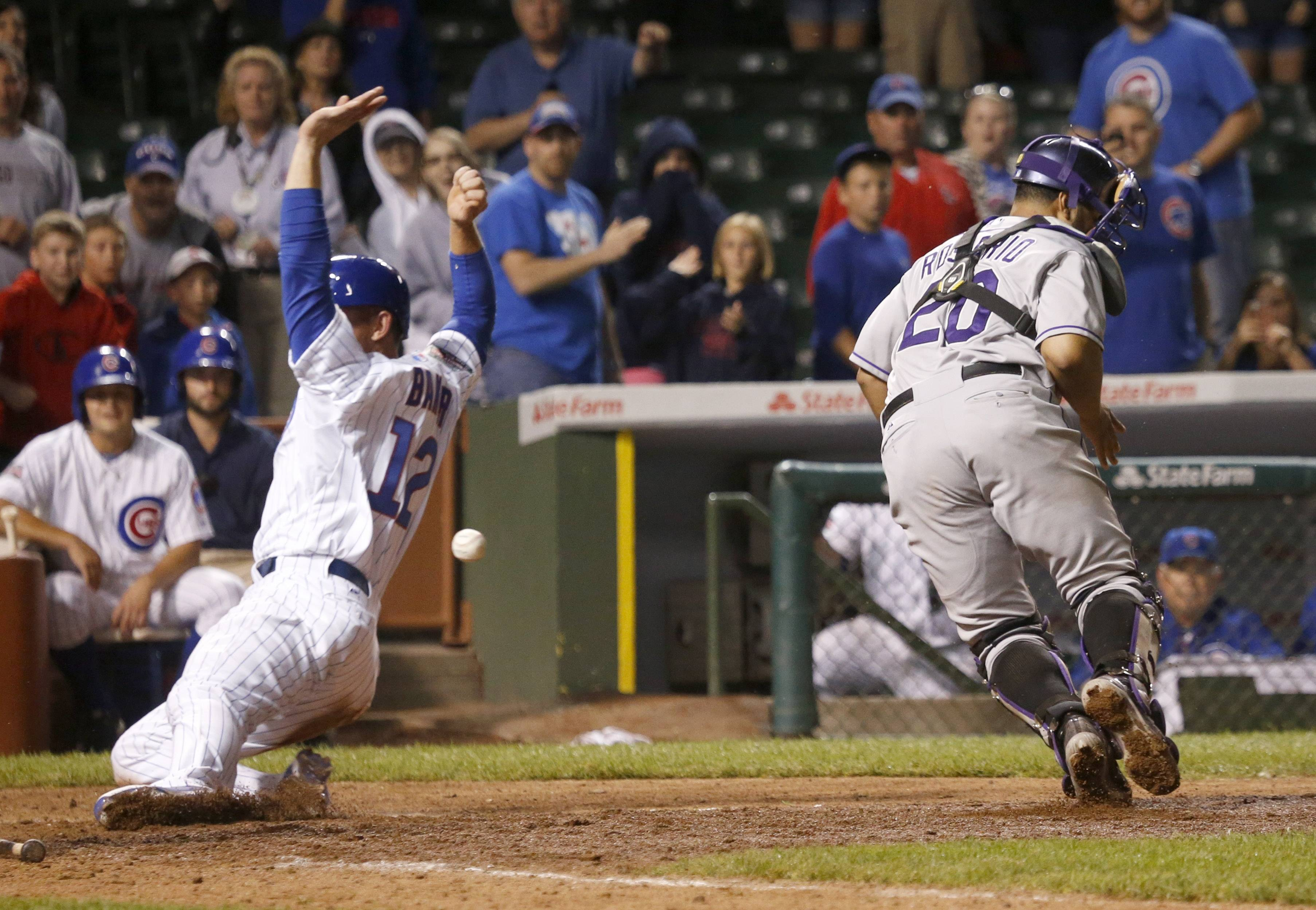 The Cubs' John Baker, left, scores the game winning run off a sacrifice fly by Starlin Castro, as the ball gets past Colorado Rockies catcher Wilin Rosario during the 16th inning Wednesday in Chicago. The Cubs' won 4-3 and Baker got the win for pitching the 16th inning.