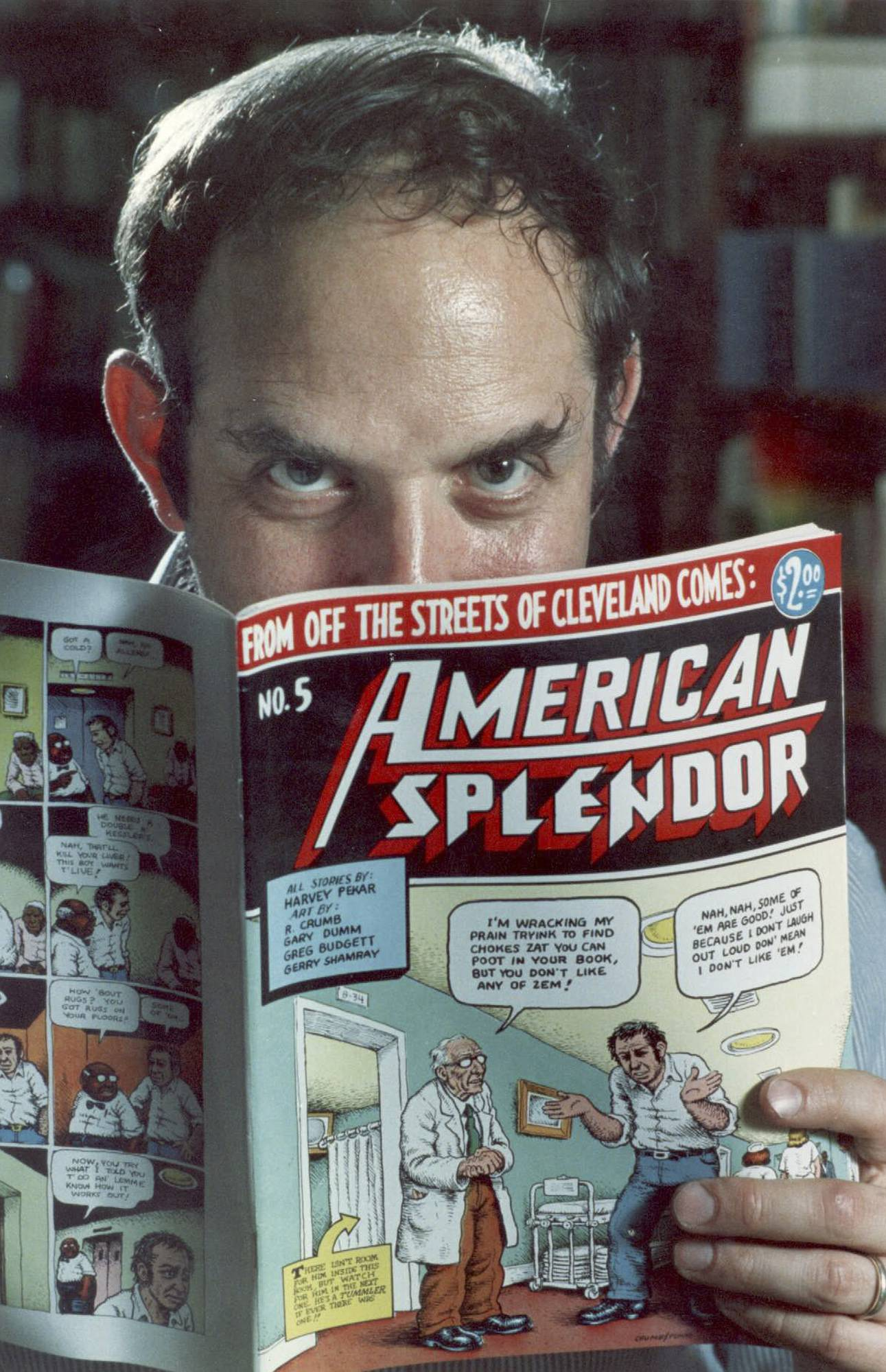 "In this 1986 file photo, comic-book writer Harvey Pekar poses with a copy of ""American Splendor"" in his Cleveland Heights, Ohio, home. Pekar's comic was made into a 2003 film starring Paul Giamatti."