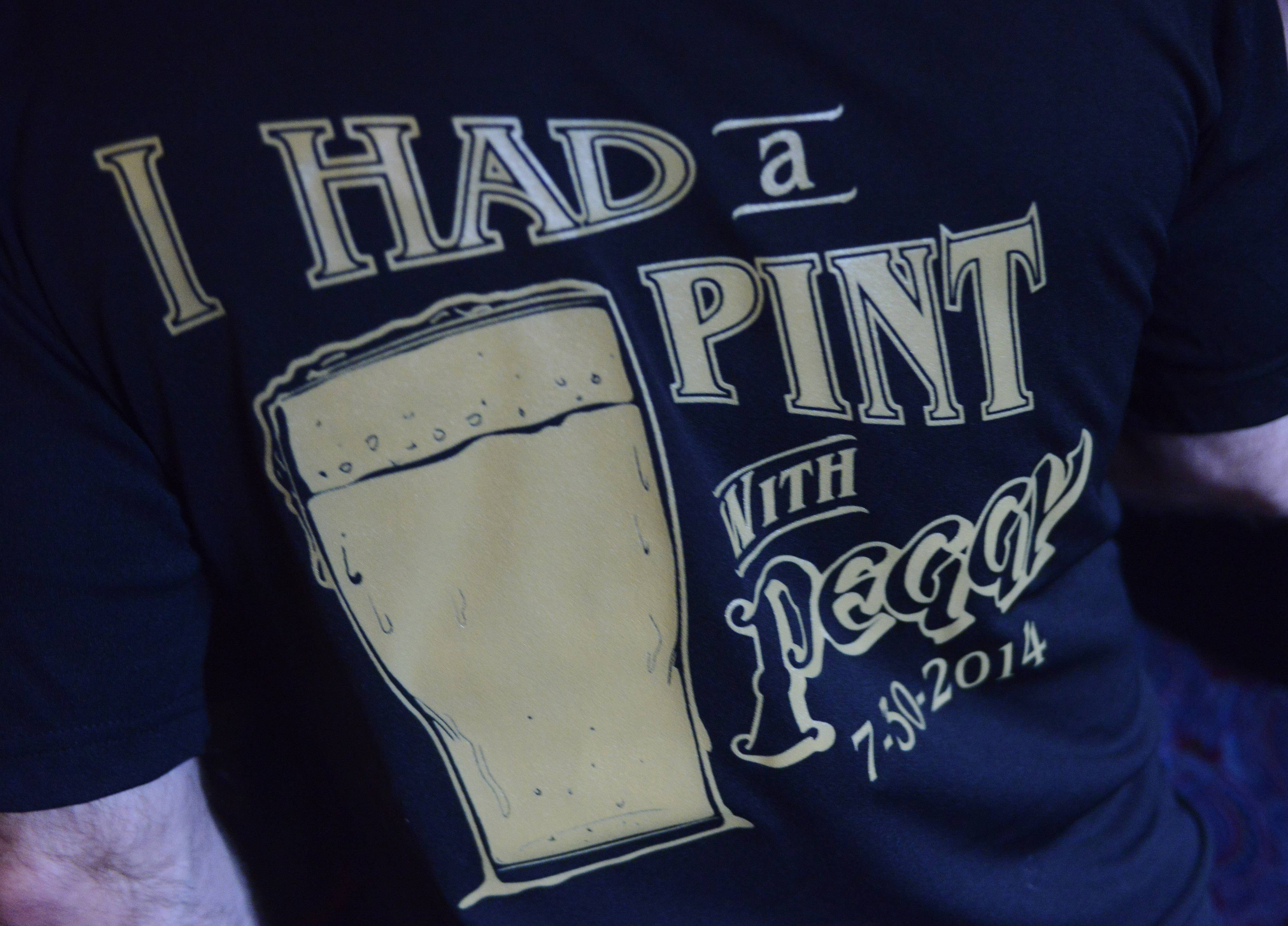 """I Had a Pint With Peggy"" T-shirts were being distributed during a visit Wednesday night from by Peggy Kinnane, 75, namesake of Peggy Kinnane's Irish Restaurant & Pub in Arlington Heights."