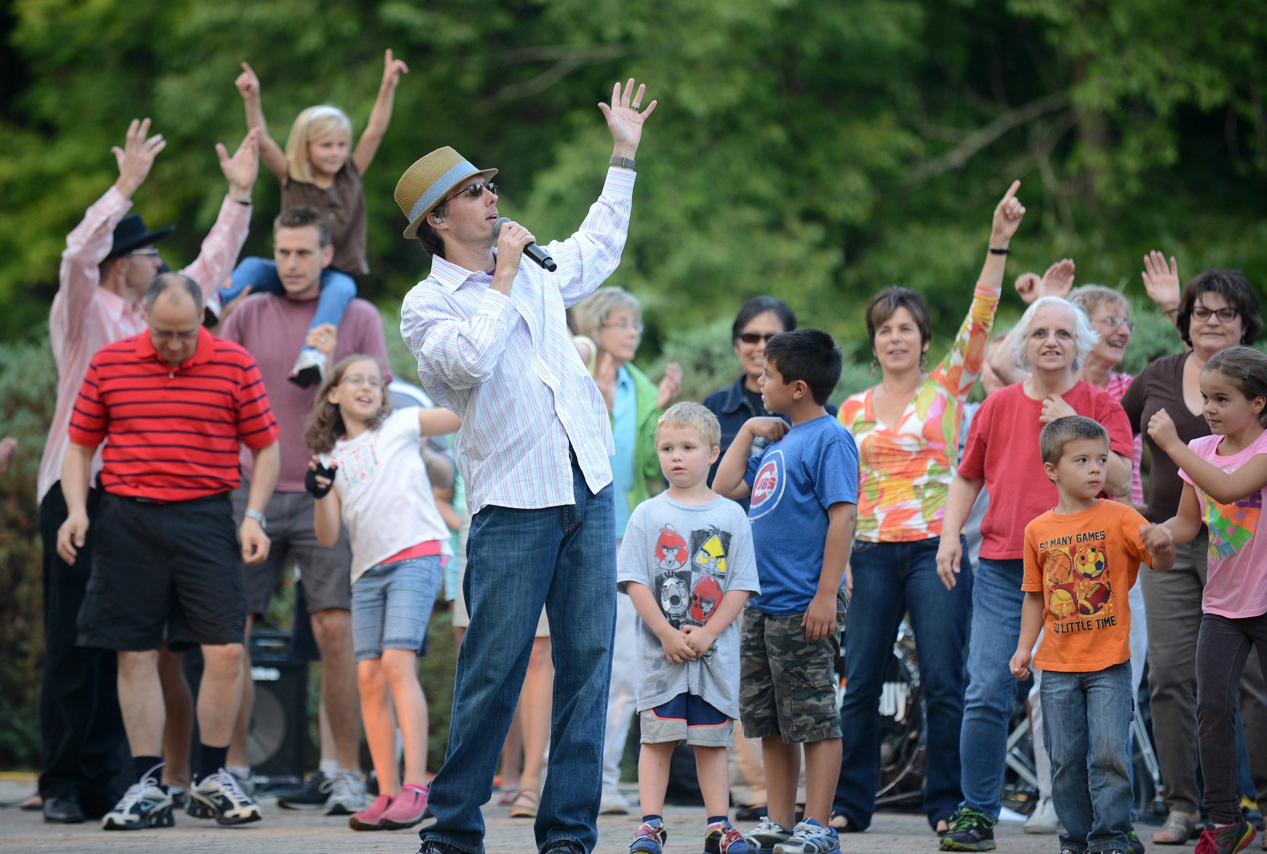 "Joe Cashman of Palos Park, lead singer of The Hat Guys, has the crowd as backup after joining the band onstage during their performance Wednesday at Island Park in Geneva on Wednesday. This was the final concert for the ""Concert in the Park"" series this month."