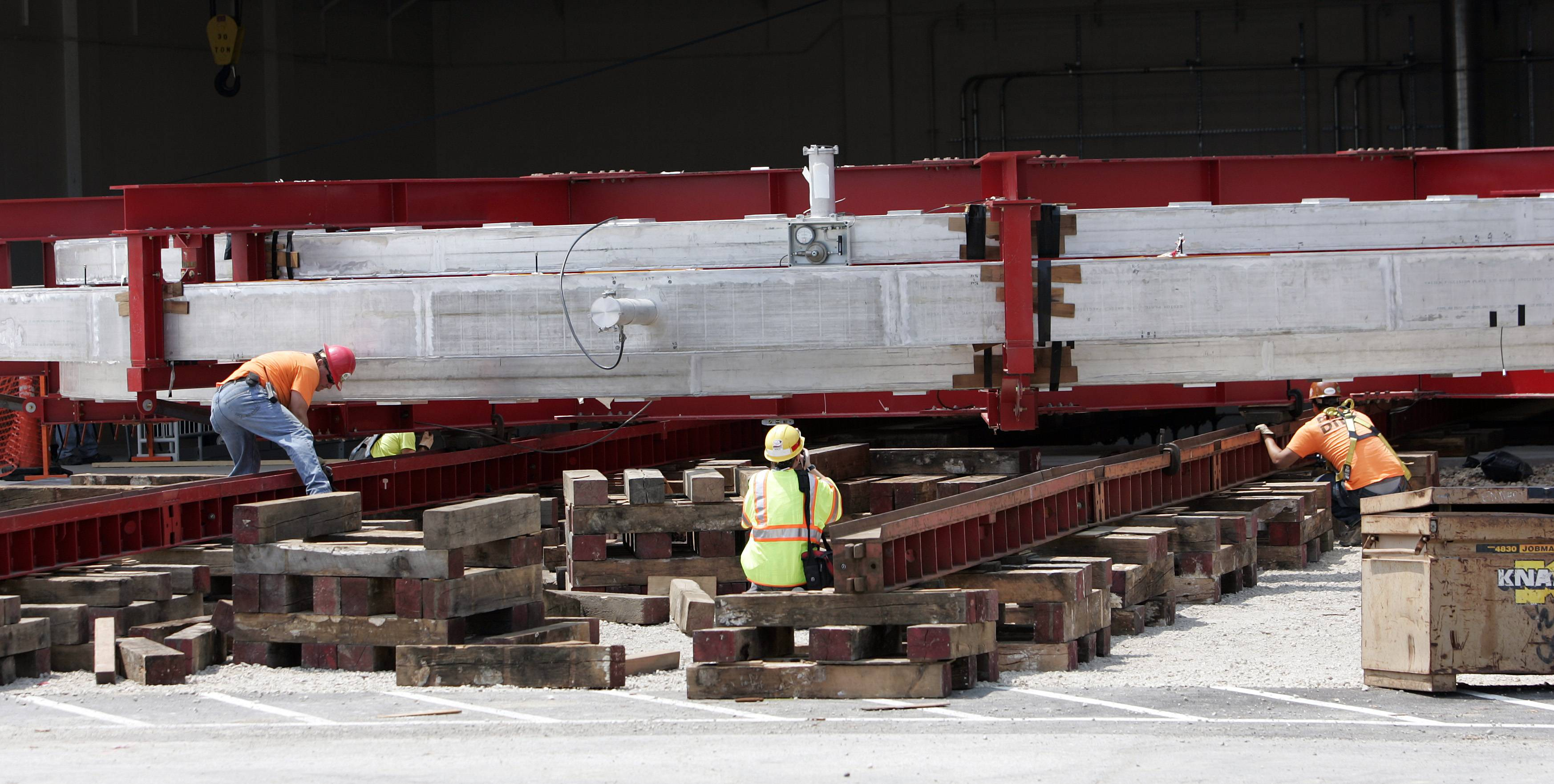 Workers make adjustments  as the gigantic Muon g-2 electromagnet, which traveled from the East Coast to Fermilab a year ago, is moved Wednesday into its new building in Batavia.