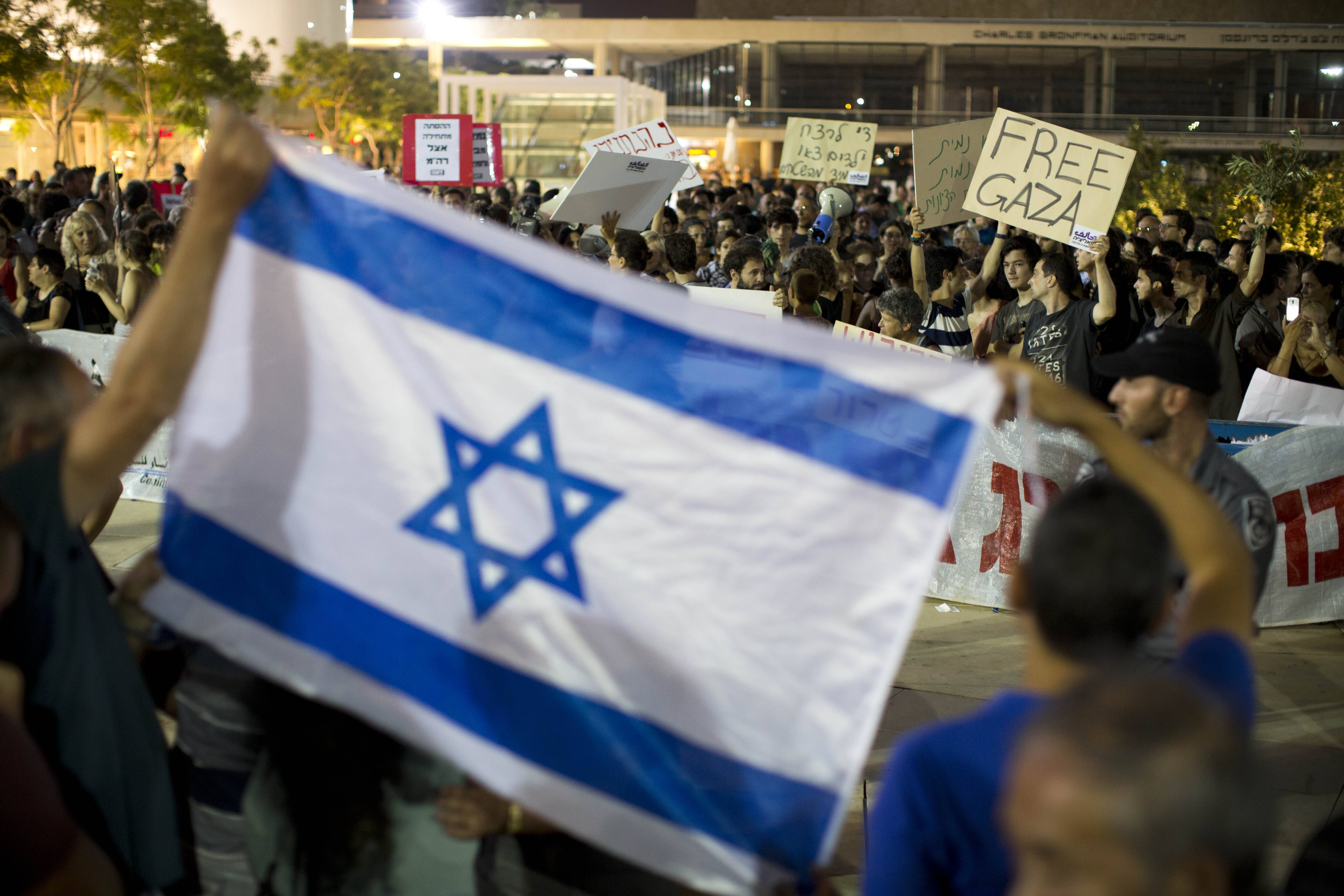 Israeli left-wing activists hold signs during a demonstration against Israel's operation in Gaza, as right-wing activists hold the Israeli flag in support of the offensive, in Tel Aviv, Israel, July 19.