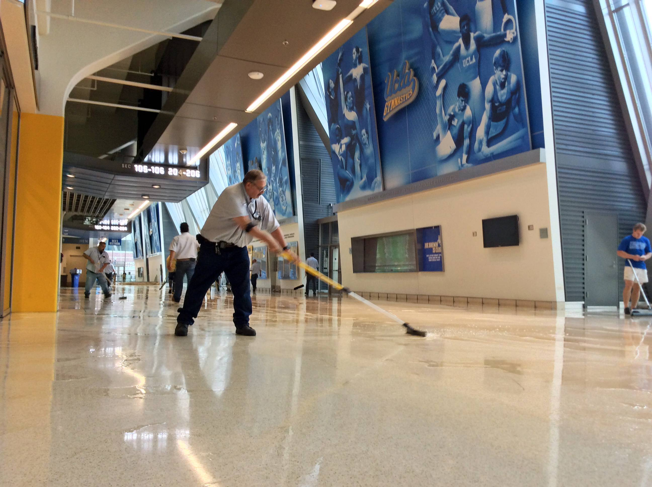A worker clears water from the lobby floor of Pauley Pavilion, home of UCLA basketball, after a 30-inch water main burst on nearby Sunset Boulevard Tuesday, July 29, 2014, in Los Angeles. Water also reached the playing floor of the basketball arena.