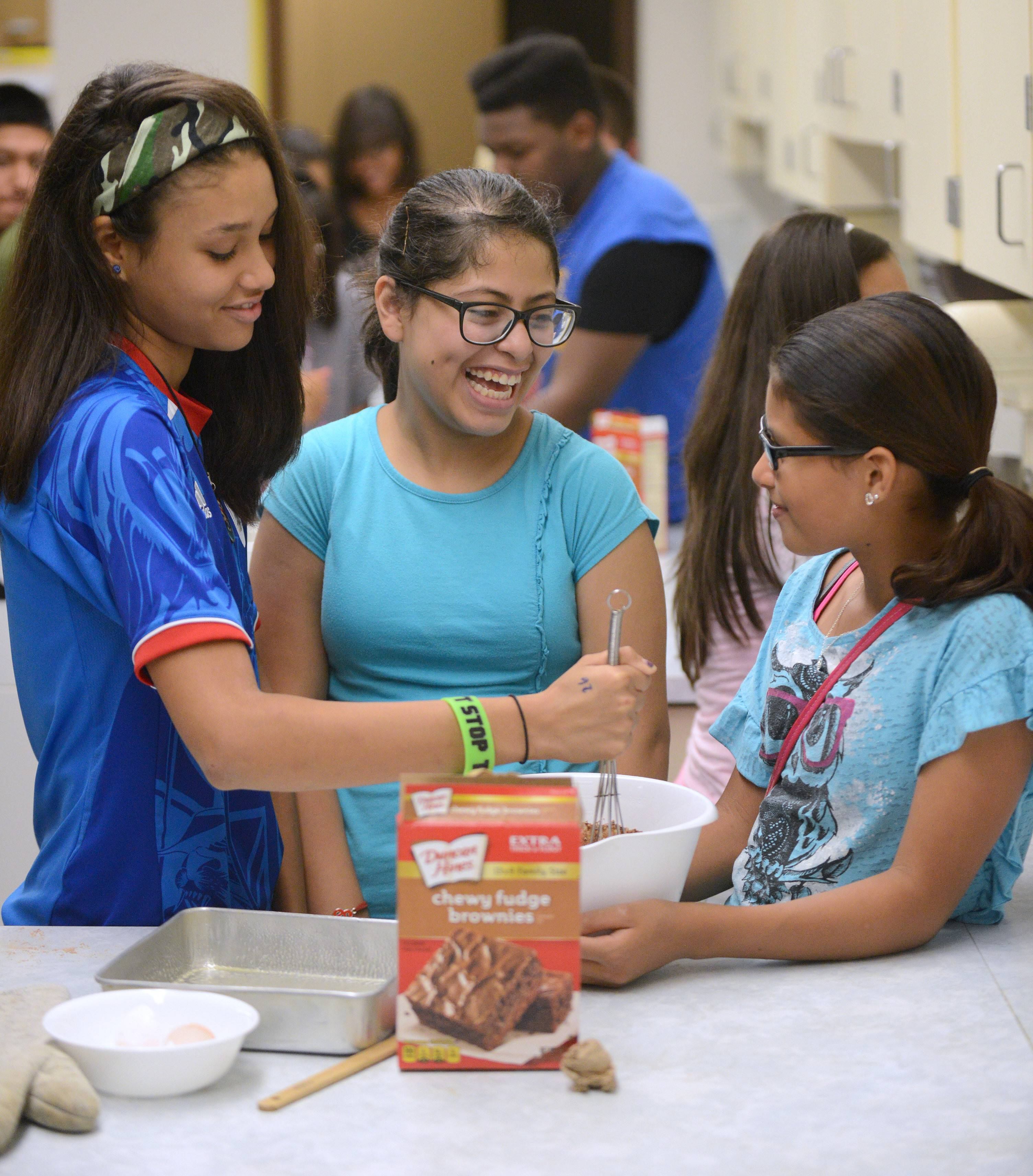 Yamaira Nieves, left, stirs a brownie mix while Alisha Ramos, center, and Daniela Ramirez, all 13, wait for their turn during a cooking class Tuesday at the Elgin Police Department's Kids United program at Abbott Middle School in Elgin. After dinner, they would be able to enjoy the brownies served with ice cream. Alisha has been coming to the program since she was 9.
