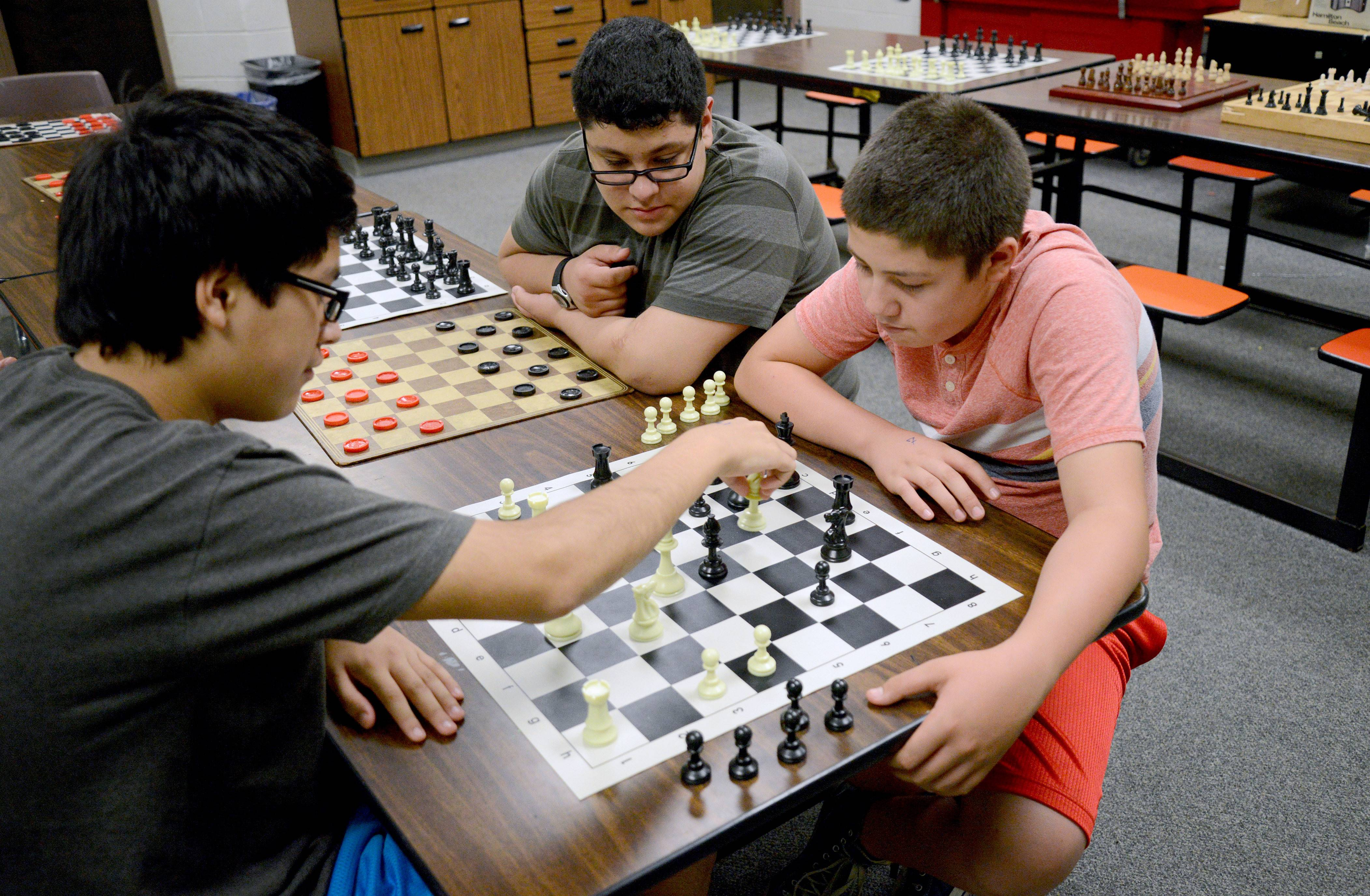 Jose Gomez, 15, left makes his move while playing against Carlos Galarza, 14, as Fabian Lechuga, 13, observes Tuesday at the Elgin Police Department's Kids United program at Abbott Middle School in Elgin. Jose has been coming to the program since he was 8 years old. Now the minimum age to attend is 9.