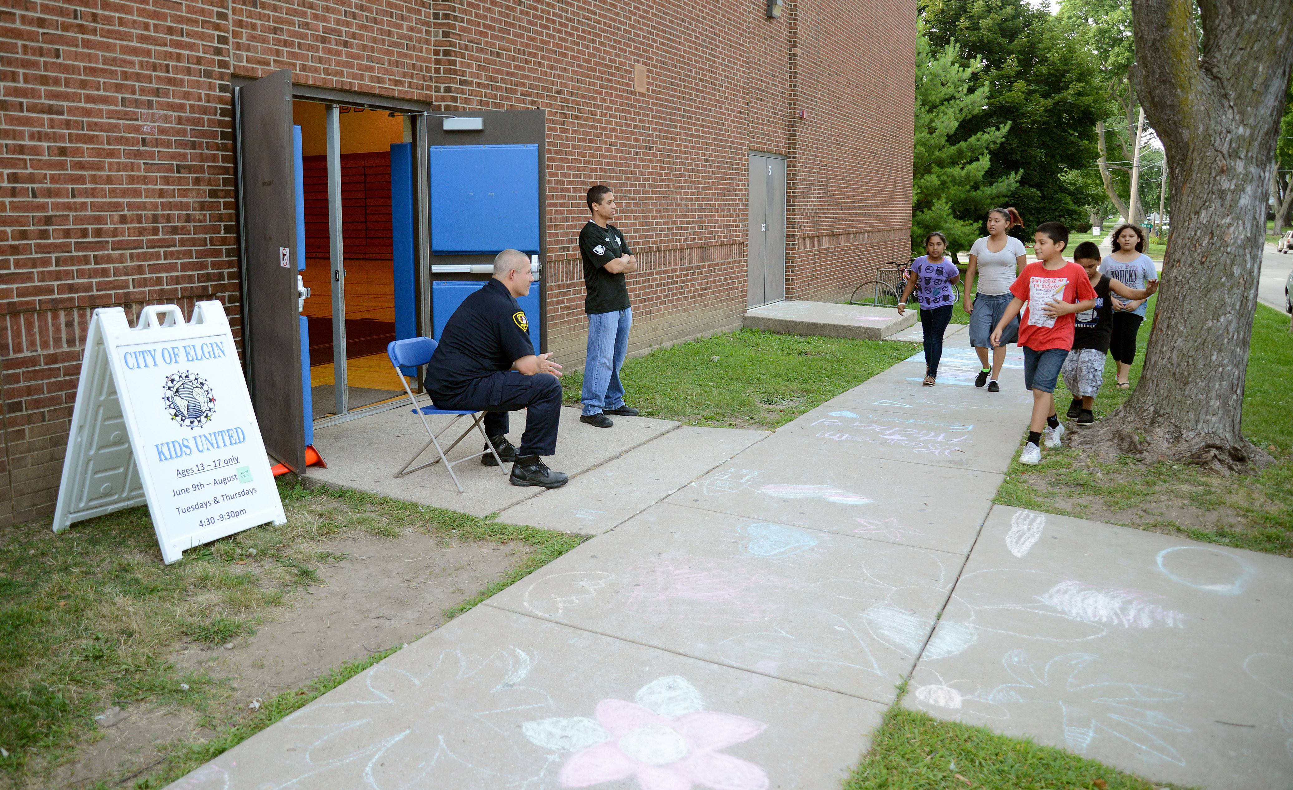 Elgin police officers talk to kids Tuesday as they walk past the entrance to the police department's Kids United program at Abbott Middle School in Elgin. A couple of the children made the drawings on the previous night. Different age groups attend on different nights of the week.