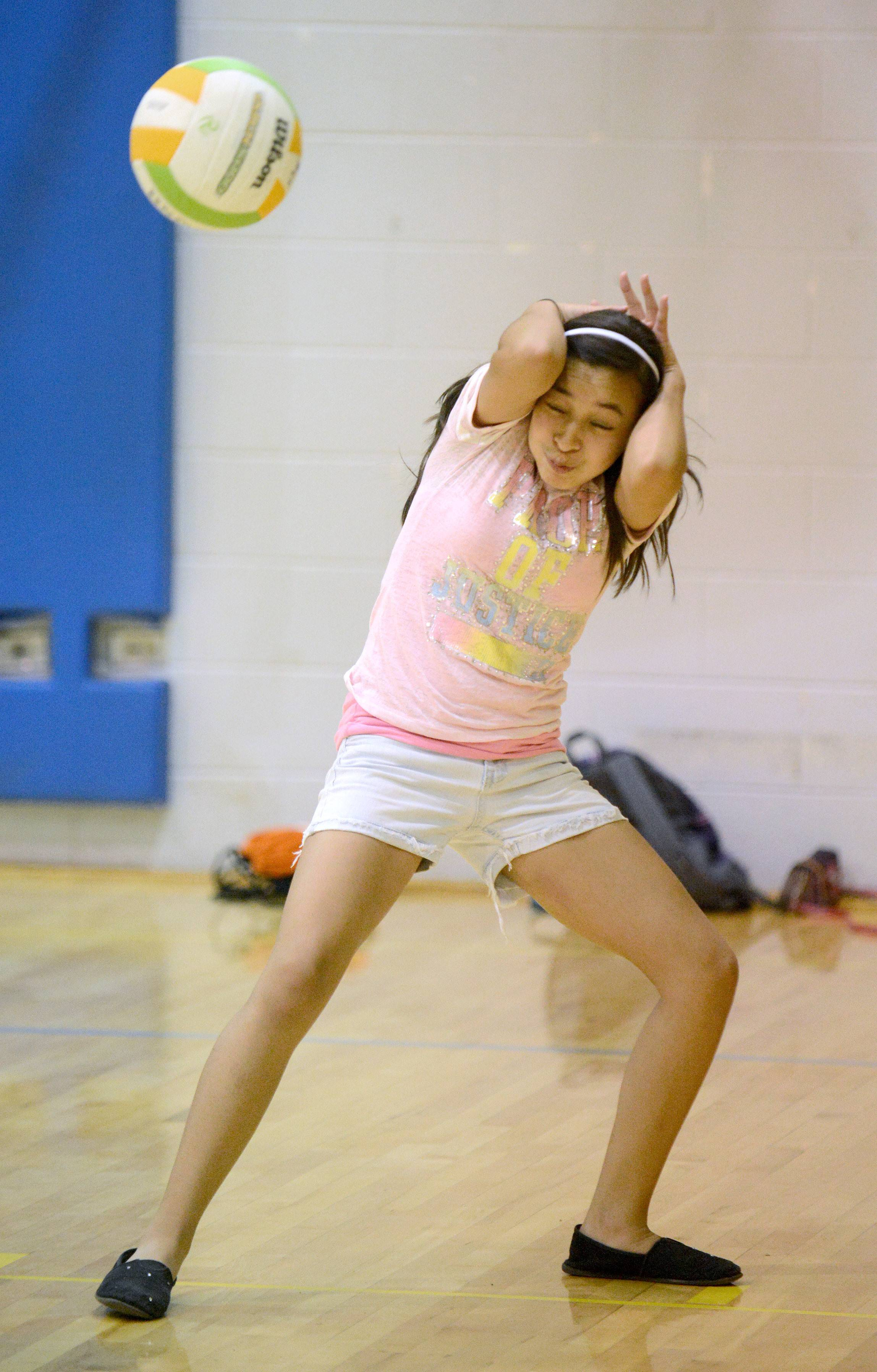 Natalie Munoz, 13, ducks while playing volleyball Tuesday at the Elgin Police Department's Kids United program at Abbott Middle School in Elgin.