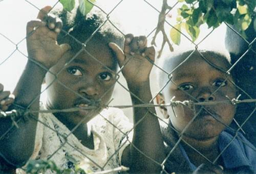 Children unable to attend Kenya Children's Fund's Kinyago-Dandora School look through the fence with longing.