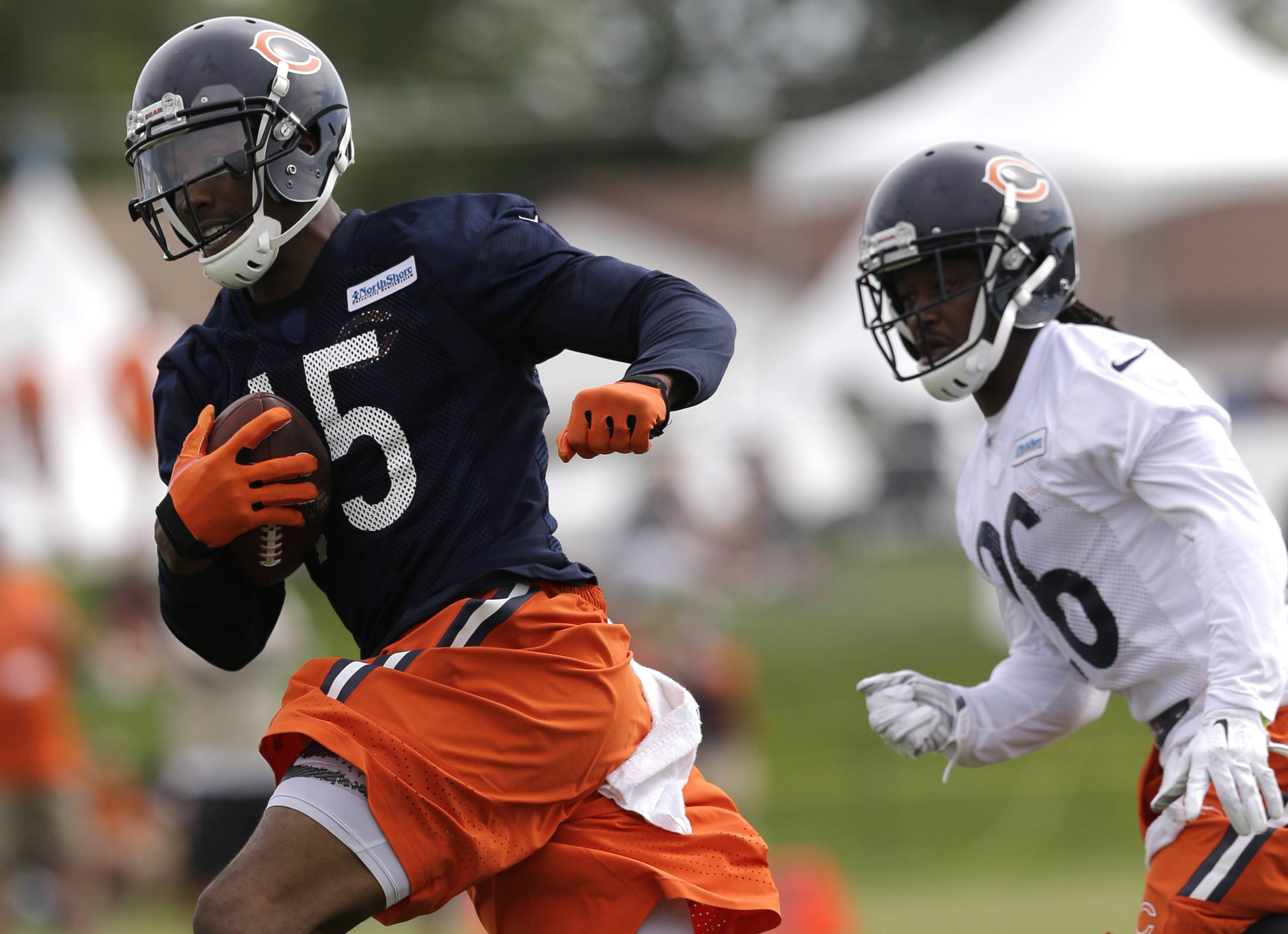Bears wide receiver Brandon Marshall runs past cornerback Tim Jennings during a training-camp workout.