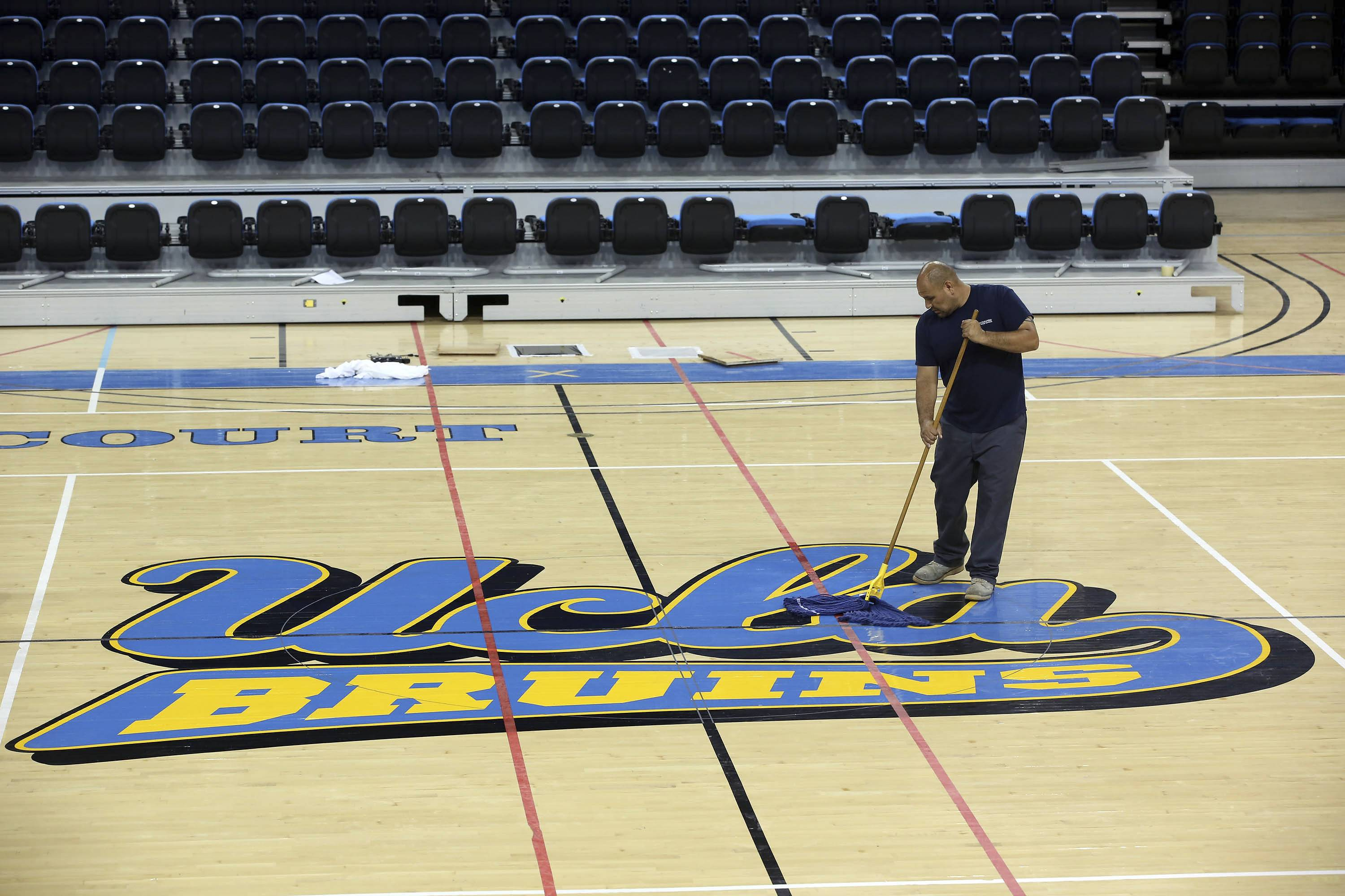 Worker Ruben Monter mops up the floor at Pauley Pavillion Wednesday July 30, 2014 in Los Angeles. A ruptured 93-year-old water main on Tuesday left the UCLA campus awash in 8 million gallons of water in the middle of California's worst drought in decades, stranding people in parking garages and flooding the school's storied basketball court less than two years after a major renovation.