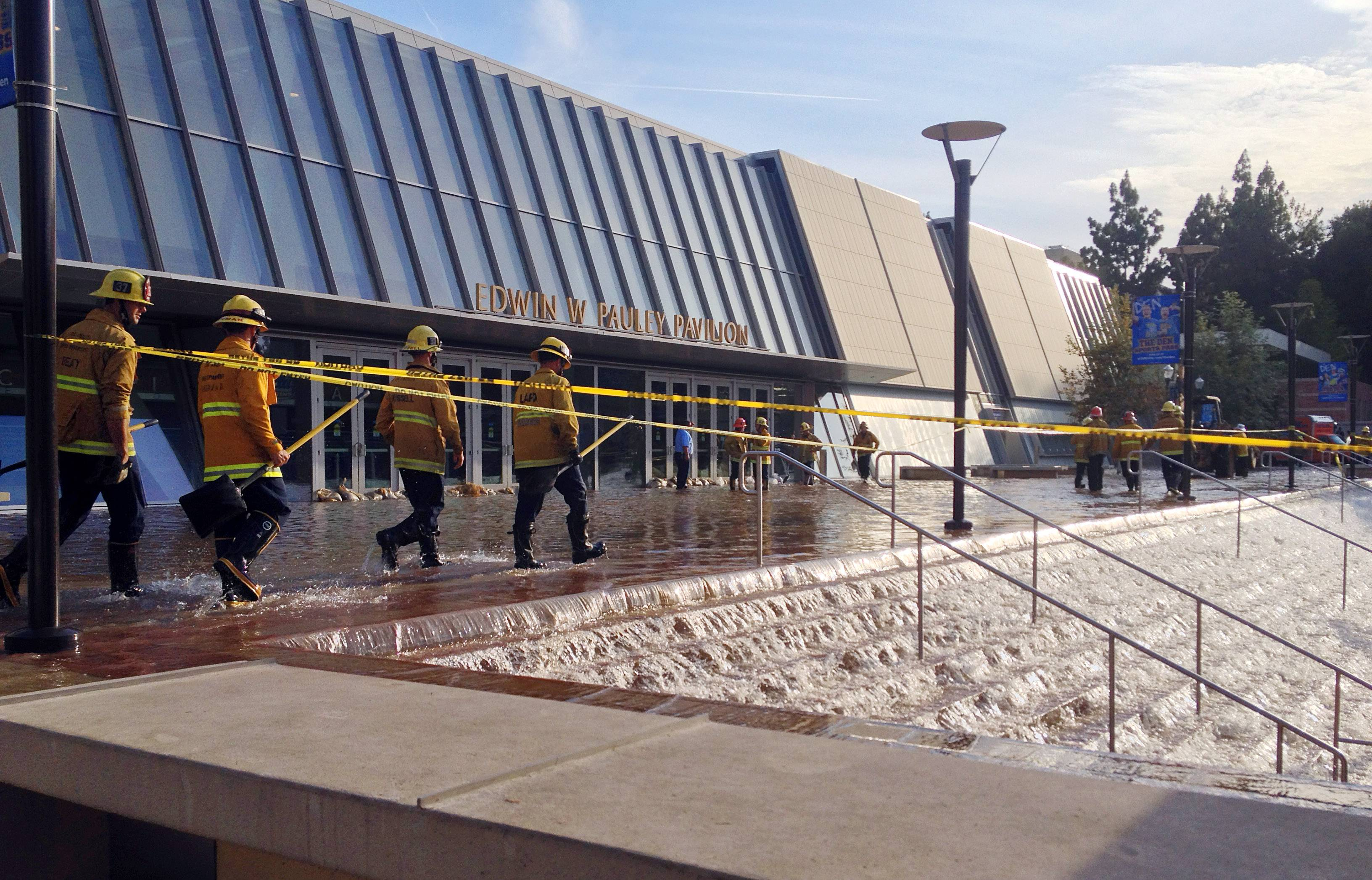 Water cascades down the stairs to a parking structure adjacent to the main entry doors of Pauley Pavilion, home of UCLA basketball, left, after a 30-inch water main burst on nearby Sunset Boulevard Tuesday, July 29, 2014, in Los Angeles. Water also reached the playing floor of the basketball arena.