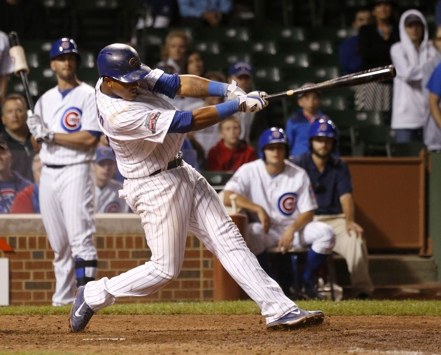 Chicago Cubs' Starlin Castro hits a game winning sacrifice fly off a pitch from Colorado Rockies relief pitcher Tyler Matzek, scoring John Baker, during the 16th inning of a baseball game Wednesday, July 30, 2014, in Chicago. The Cubs' won 4-3.