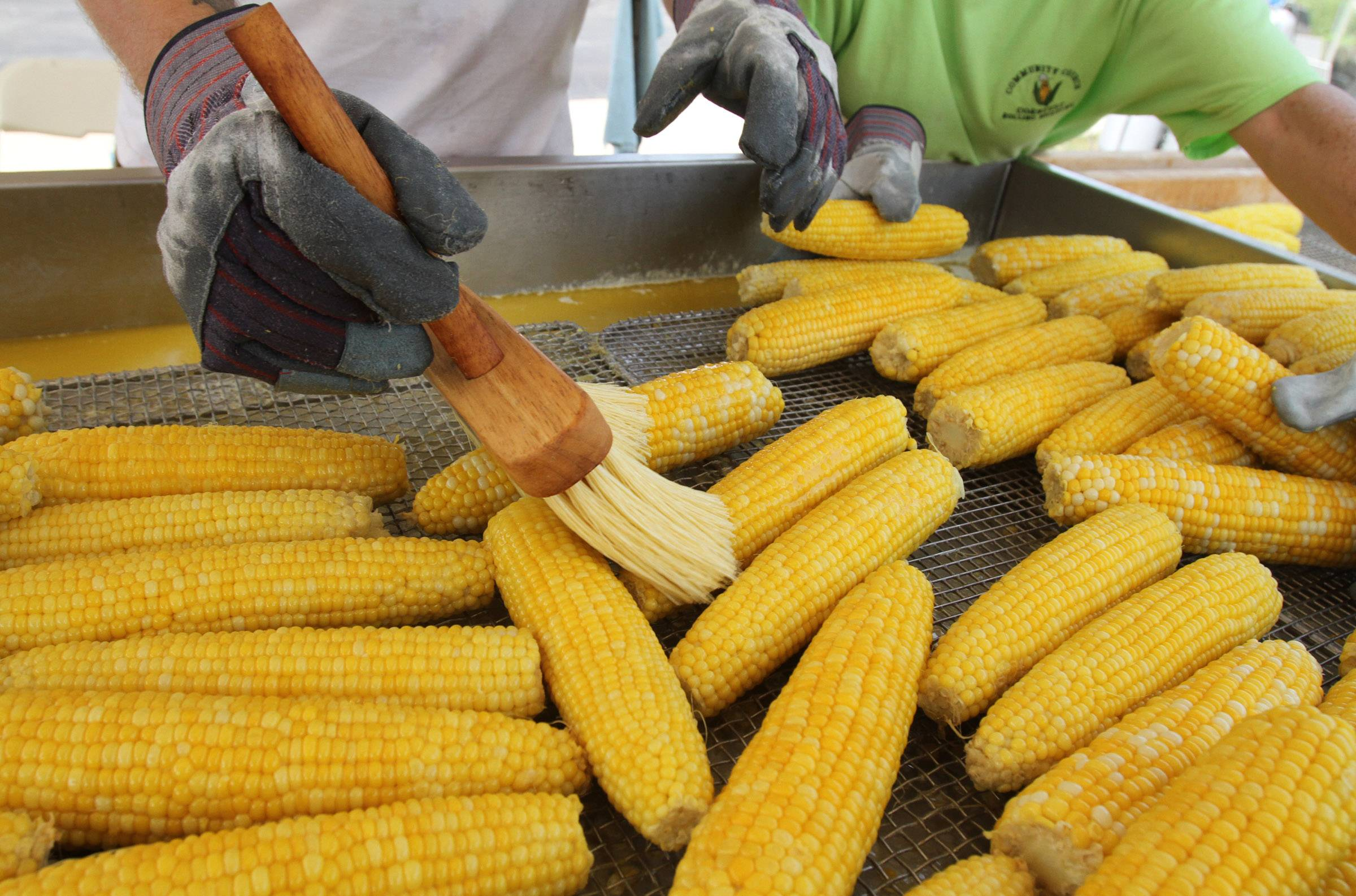 A worker butters corn at Community Church of Rolling Meadows 56th annual Corn Fest.