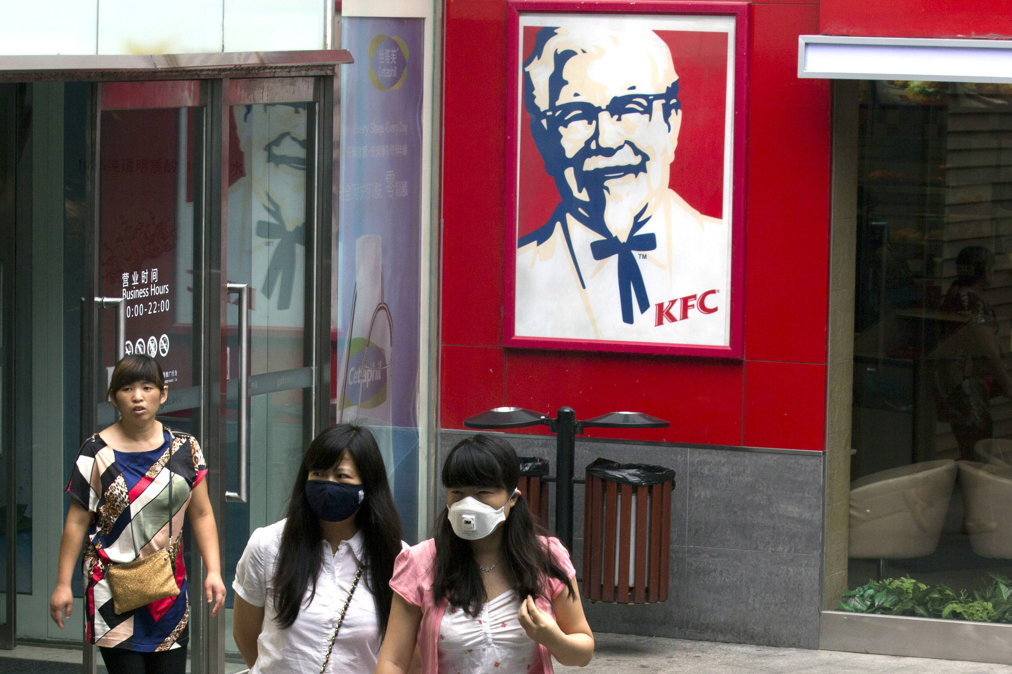 Women wearing masks during a polluted day walk outside a KFC restaurant in Beijing, China, Thursday, July 31, 2014. Already China's biggest restaurant operator with 4,600 outlets, KFC the Louisville, Kentucky-based chain is reeling after a Chinese supplier was accused of selling expired beef and chicken to it, McDonald's and possibly other restaurant chains. Just 18 months earlier, KFC's sales plunged in China after a supplier violated rules on drug use in chickens.(AP Photo/Ng Han Guan)