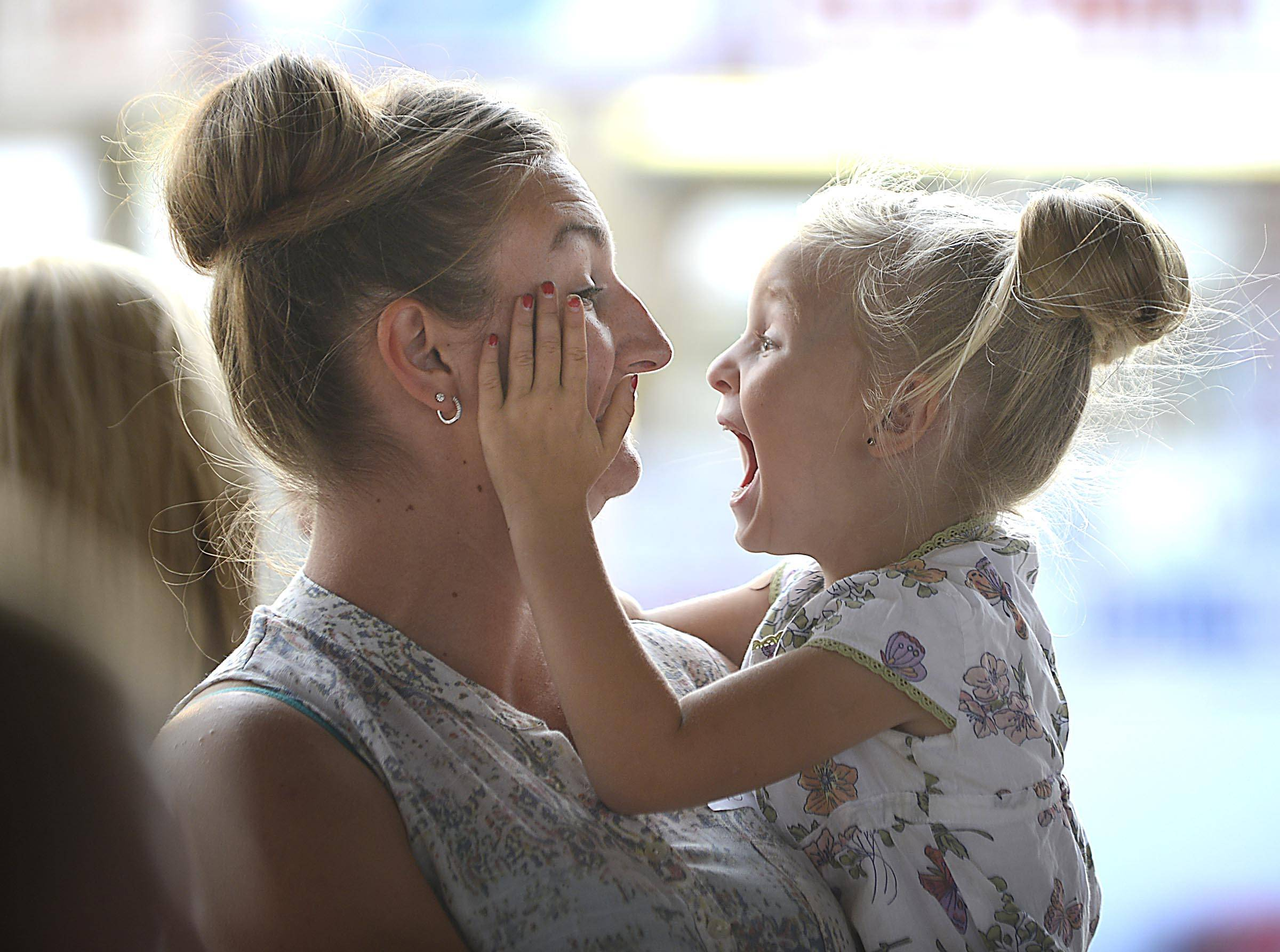 Heidi and Teagan Vanderstappen of Hebron snuggle as they wait their turn onstage during the Mother/Daughter Look-Alike contest in the Hansen Pavilion Thursday at the McHenry County Fair. Teagan, 4, often puts her hair up like her mother's, she said.