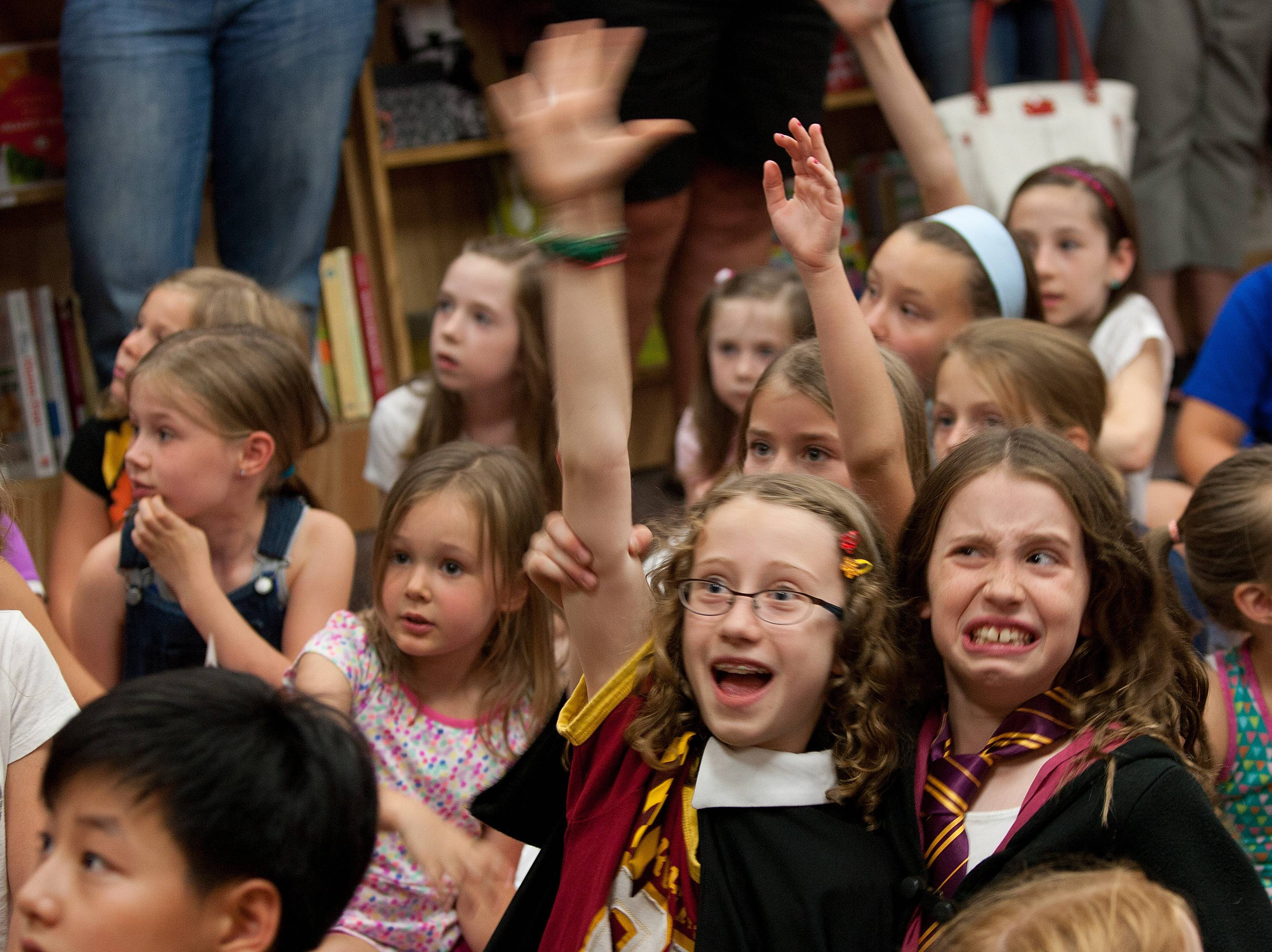 "Tabitha Irvin, 9, of Downers Grove, right, raises the hand of her friend Alyssa Bonheyo, 10, of Downers Grove during ""Harry Potter"" trivia Thursday at a party at Anderson's Bookshop in Naperville to celebrate the fictional wizard's birthday."