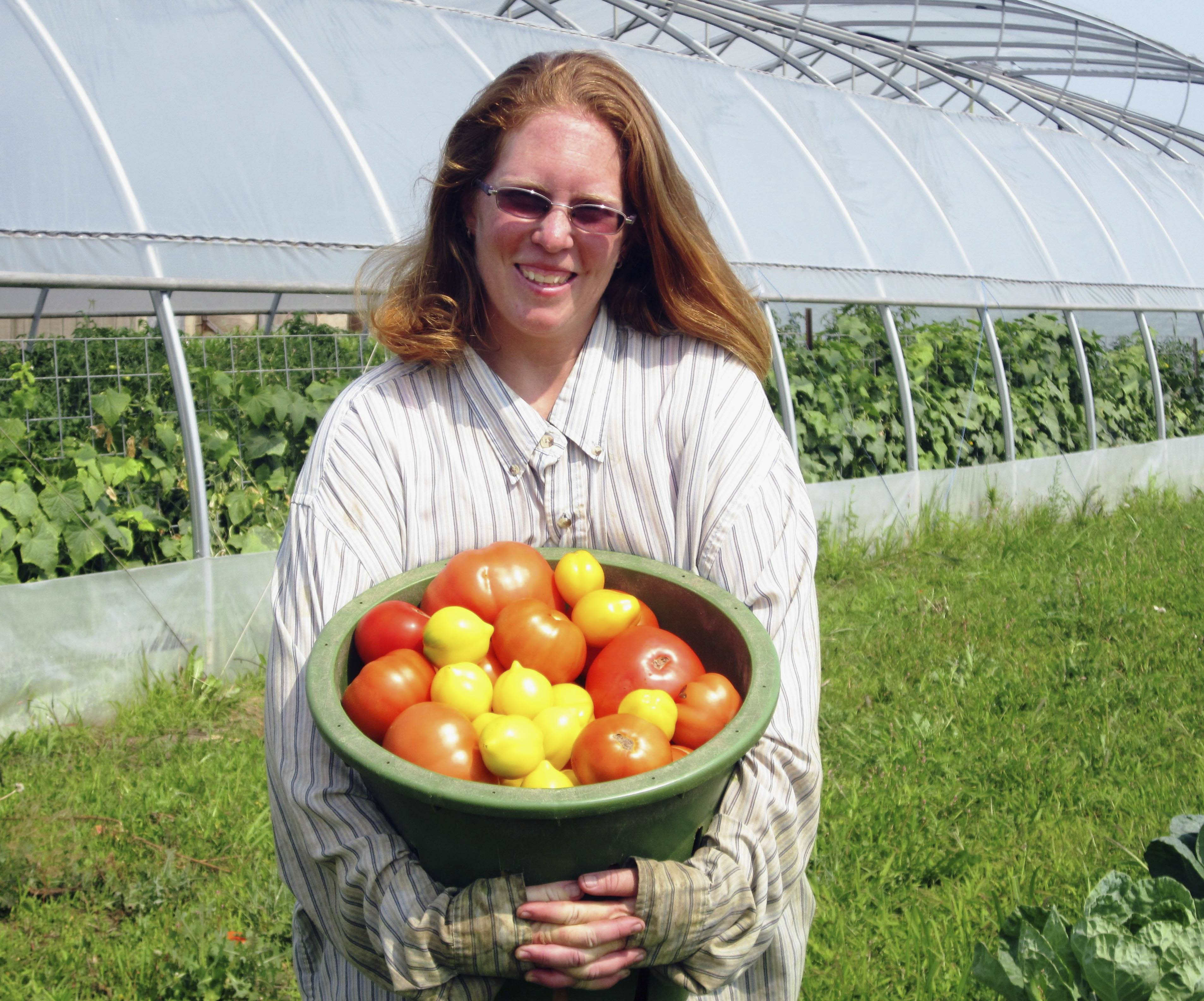 Mary Brubach, of Garden Prairie, Ill., holds up a basket of tomatoes picked to sell in the Belvidere Farmer's Market.