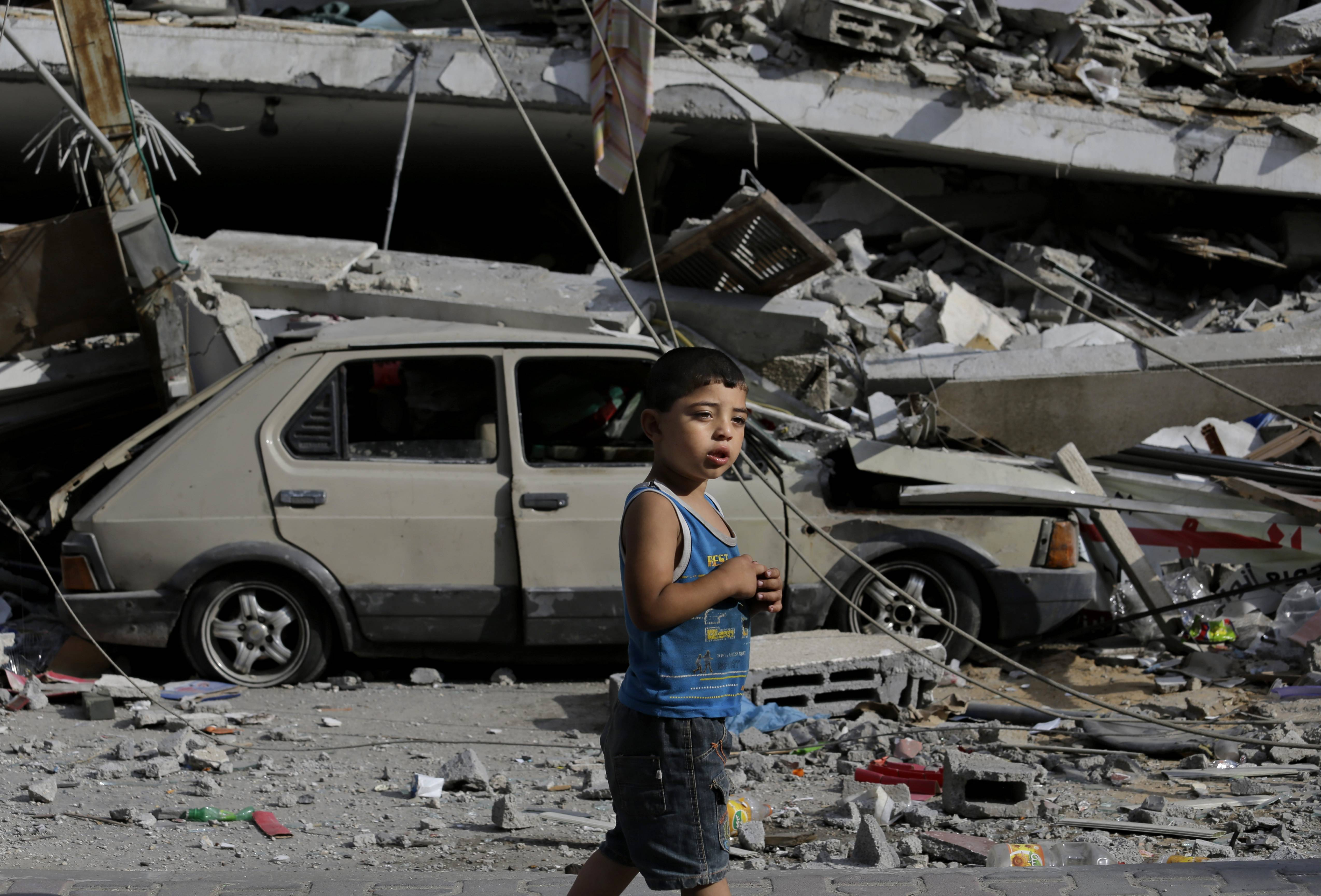 Palestinian Abdel Aziz Jendiyah, 4, walks past a six-story building, destroyed by an Israeli strike earlier during the war, adjacent to his family house, in the Sabra neighborhood of Gaza City, northern Gaza Strip, Thursday. The Jendiyah family building houses 21 members of the extended family, and now with several rooms destroyed, they try to go about their lives, without electricity and without running water for several hours a day.