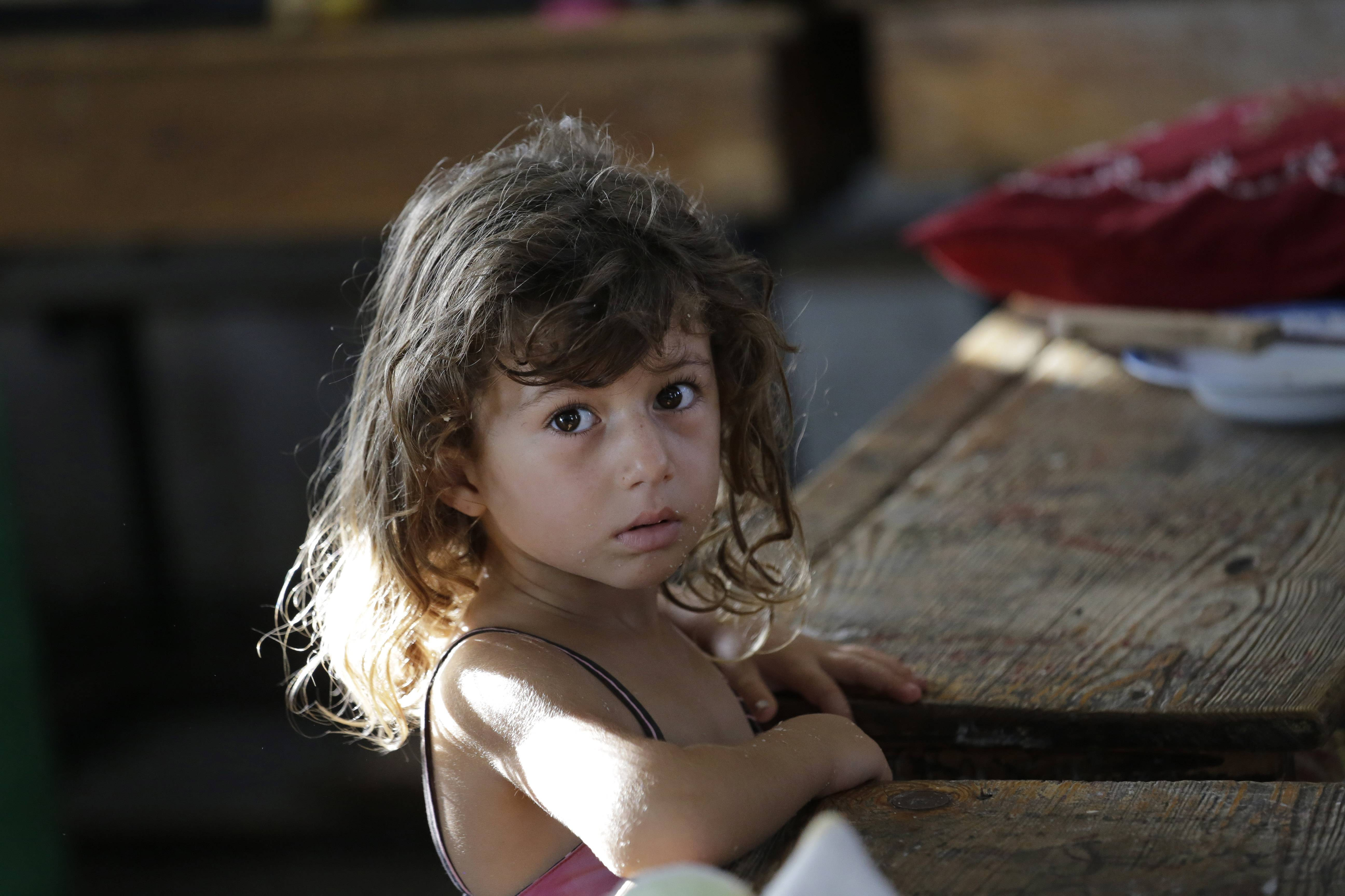 Displaced Palestinian Hajar Muharram, 5, looks on in a classroom where the family of seven now lives, at a U.N. school, in Beit Lahiya, northern Gaza Strip, on Thursday.