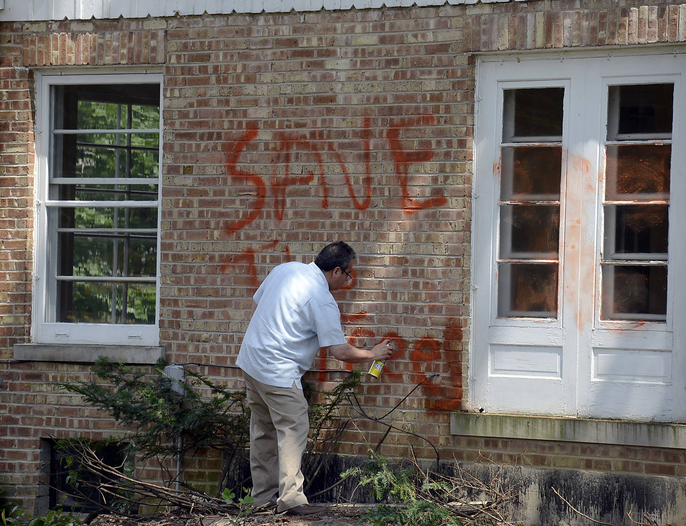 "A house on property where developers cut down trees was defaced in Rolling Meadows. Jesus Serrato of Construction Technology & Services of Palatine works to erase the bright orange spray paint saying ""Rolling Meadows, City of Trees and Save the Trees."""