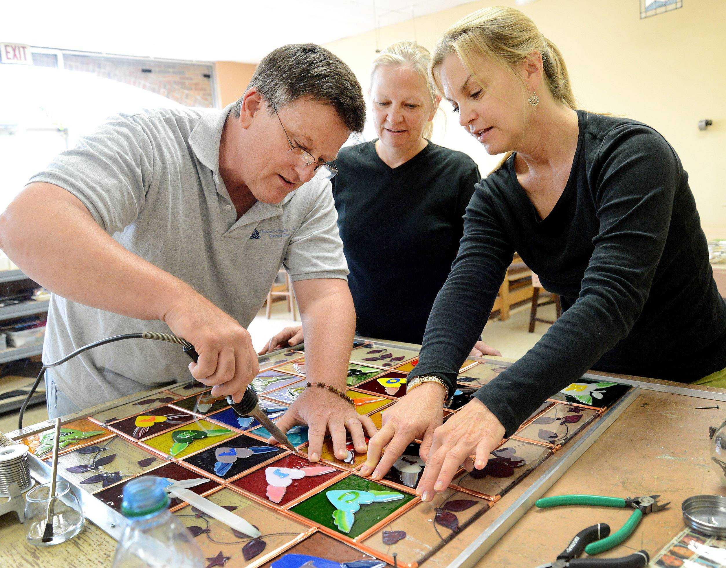 Patti Muller of New Orleans, right, is making a stained-glass quilt in remembrance of the 2012 Sandy Hook school shooting in Connecticut. Here, she works with Eric and Markay Suevel at their Arlington Heights glass studio.