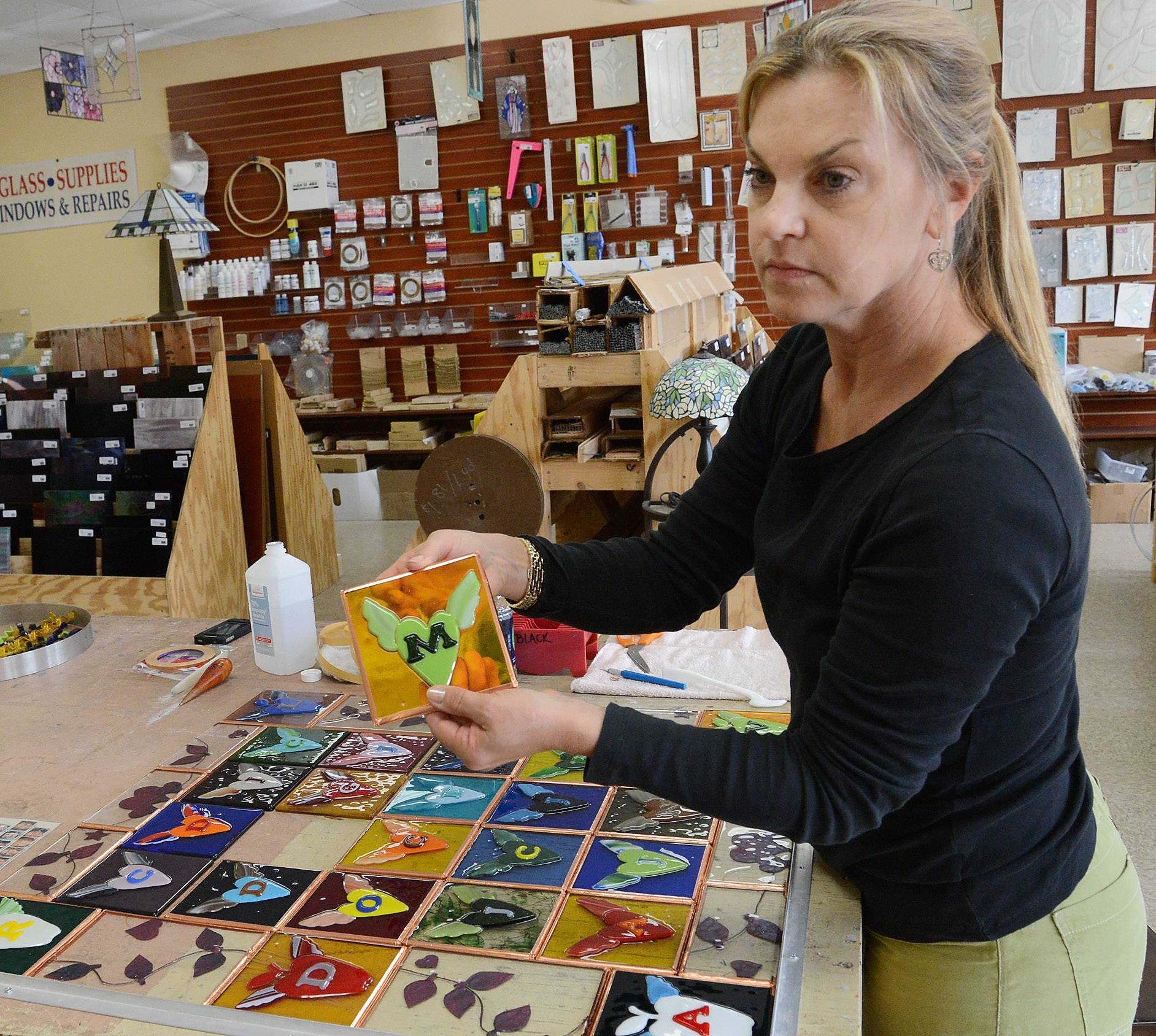 Patti Muller of New Orleans is making a stained glass quilt in remembrance of the 2012 Sandy Hook school shooting in Connecticut. She came to Suevel Studios in Arlington Heights this week to put all the pieces into one larger panel and add finishing touches.