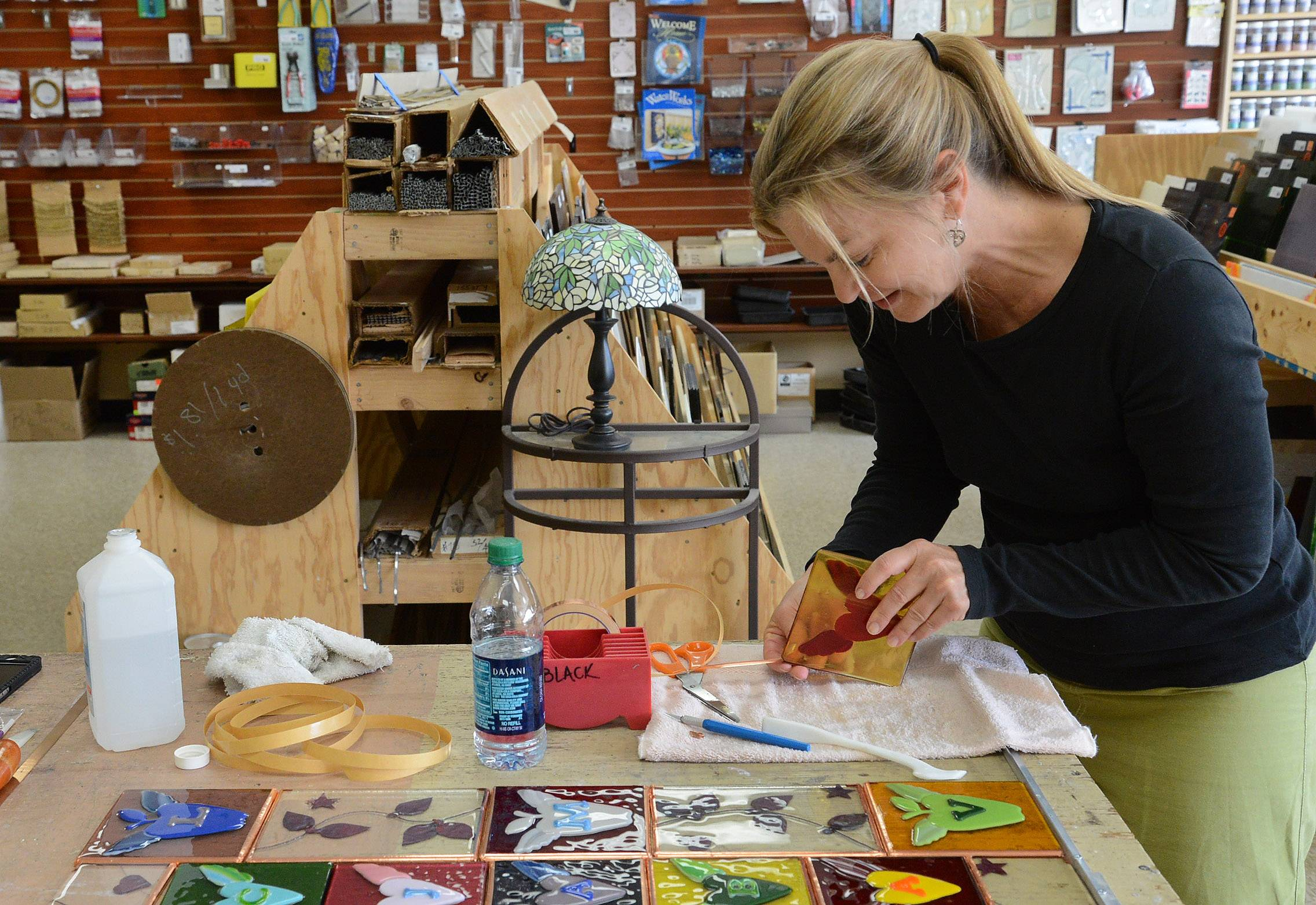 Patti Muller of New Orleans is making a stained glass quilt in remembrance of the 2012 Sandy Hook school shooting in Connecticut. Here, she is applying copper tape to the sides of each piece.