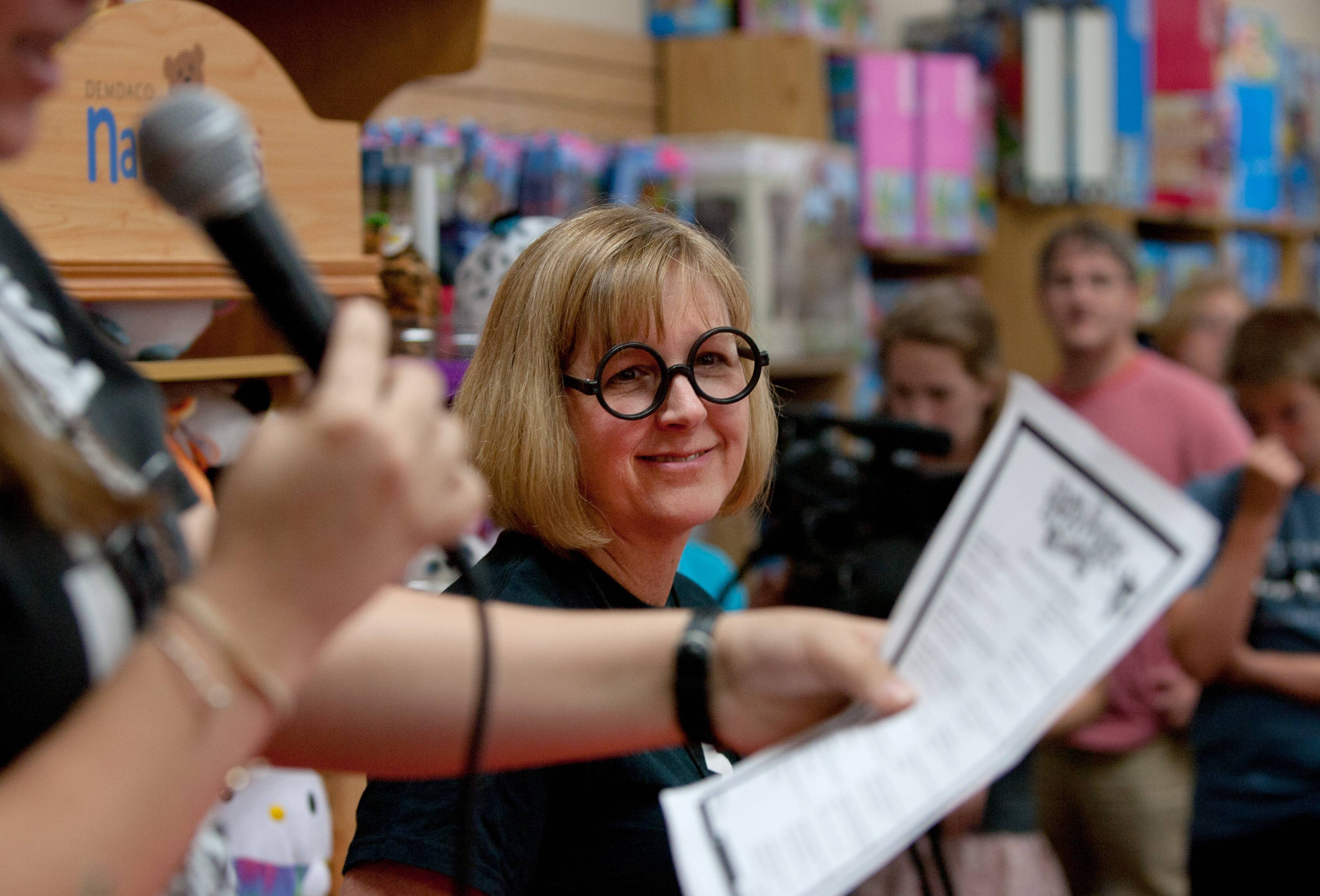 "Elizabeth Lewis of Anderson's Bookshop in downtown Naperville listens as ""Harry Potter"" birthday party attendees participate in a trivia contest. The shop celebrated the fictional wizard's birthday Thursday afternoon with cake, crafts and games."