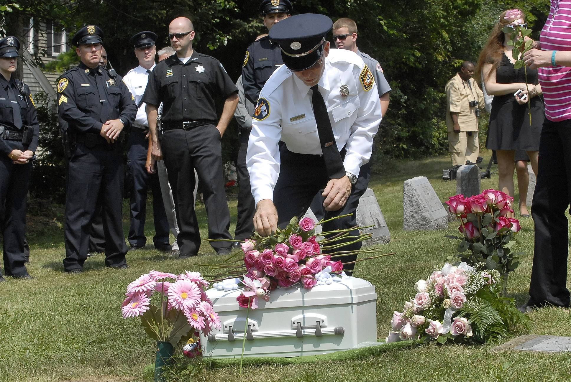 Barrington firefighters and police officers place roses on the casket of 7-month-old Mya Edwards during her burial Thursday at Evergreen Cemetery.