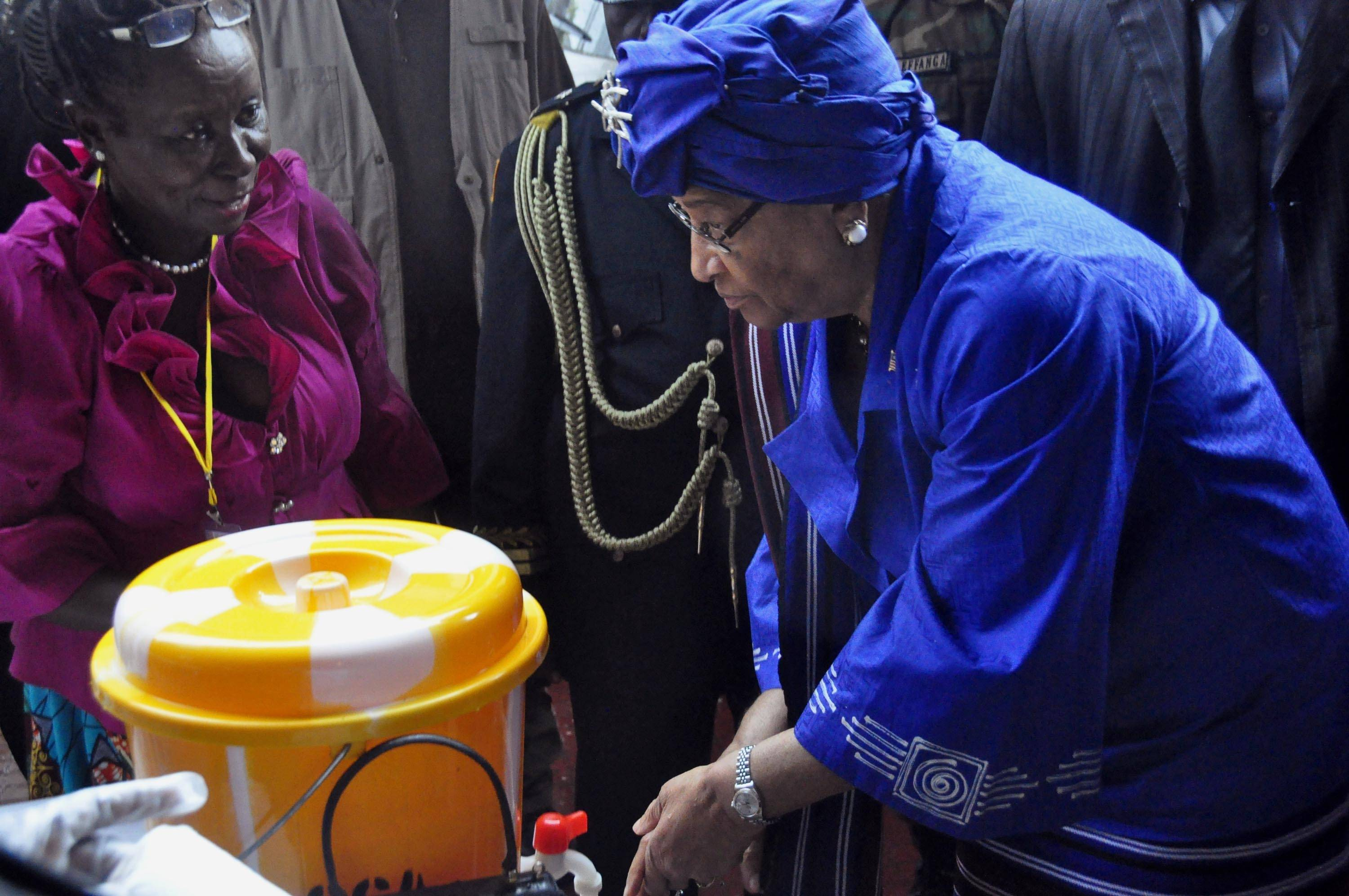 Liberia President Ellen Johnson Sirleaf, right, demonstrates to people how to wash their hands properly in order to prevent the spread of the Ebola virus, during Independence Day celebrations in the city of Monrovia, Liberia, Saturday.