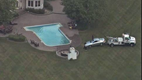 A silver 2006 Honda Coupe is towed out of a pool on Longmeadow Court in Barrington Hills on Thursday morning. A Schaumburg man was charged with driving under the influence of alcohol after police say he drove the car into the pool at about 4 a.m.