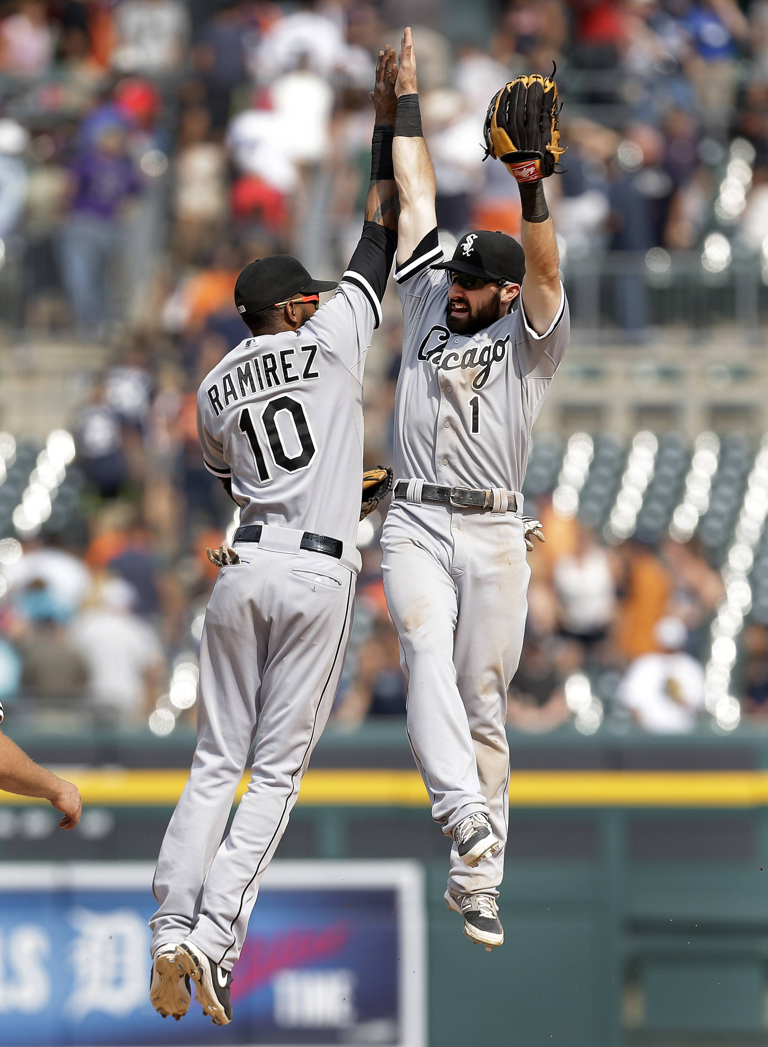 Chicago White Sox shortstop Alexei Ramirez (10) and Adam Eaton (1) celebrate their 7-4 win against the Detroit Tigers after a baseball game in Detroit,  Thursday, July 31, 2014.