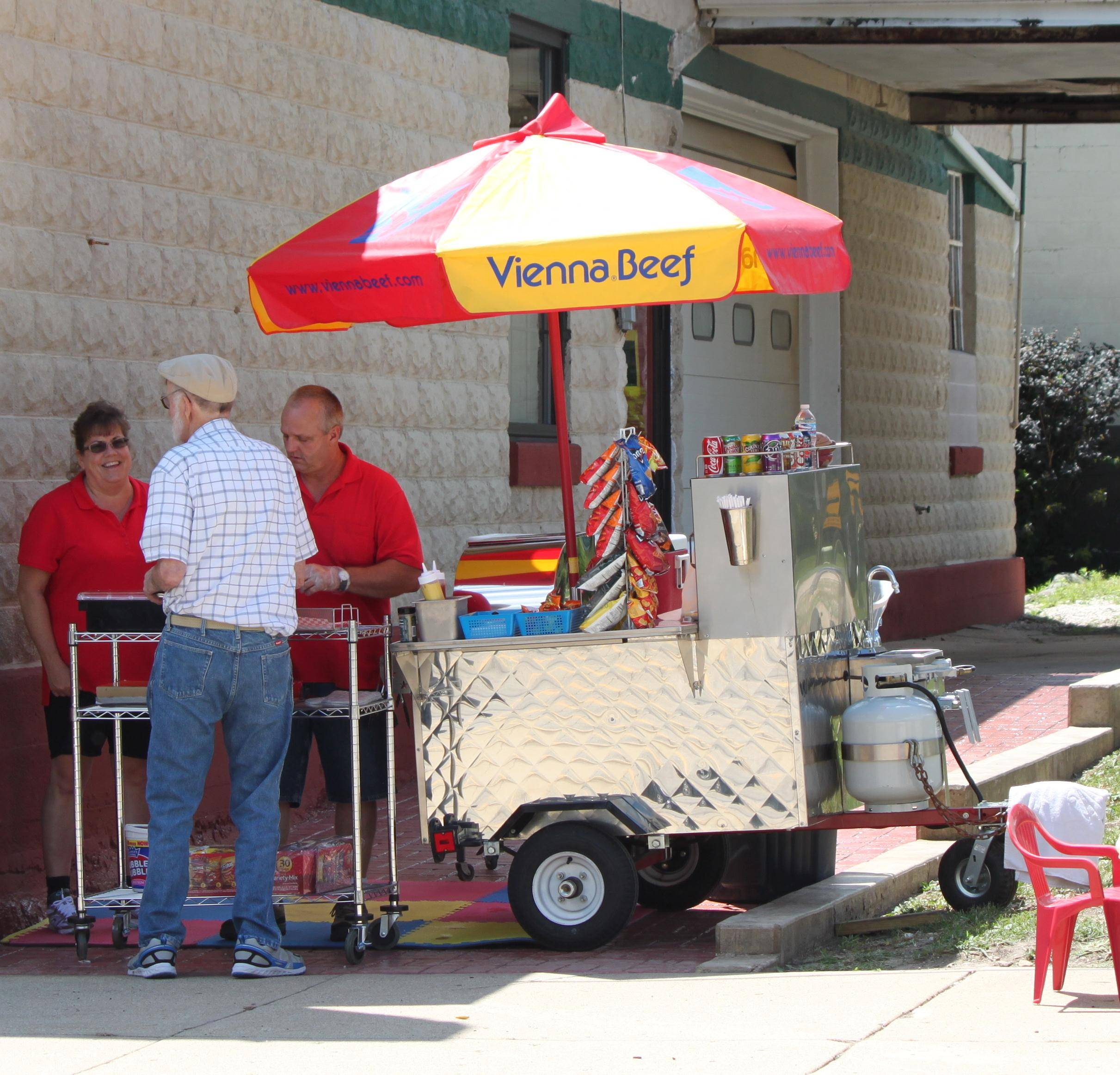 Alex and Mary Moore serving Vienna Beef Hot Dogs to one of many customers on National Hot Dog Day July 23.Mary Lake