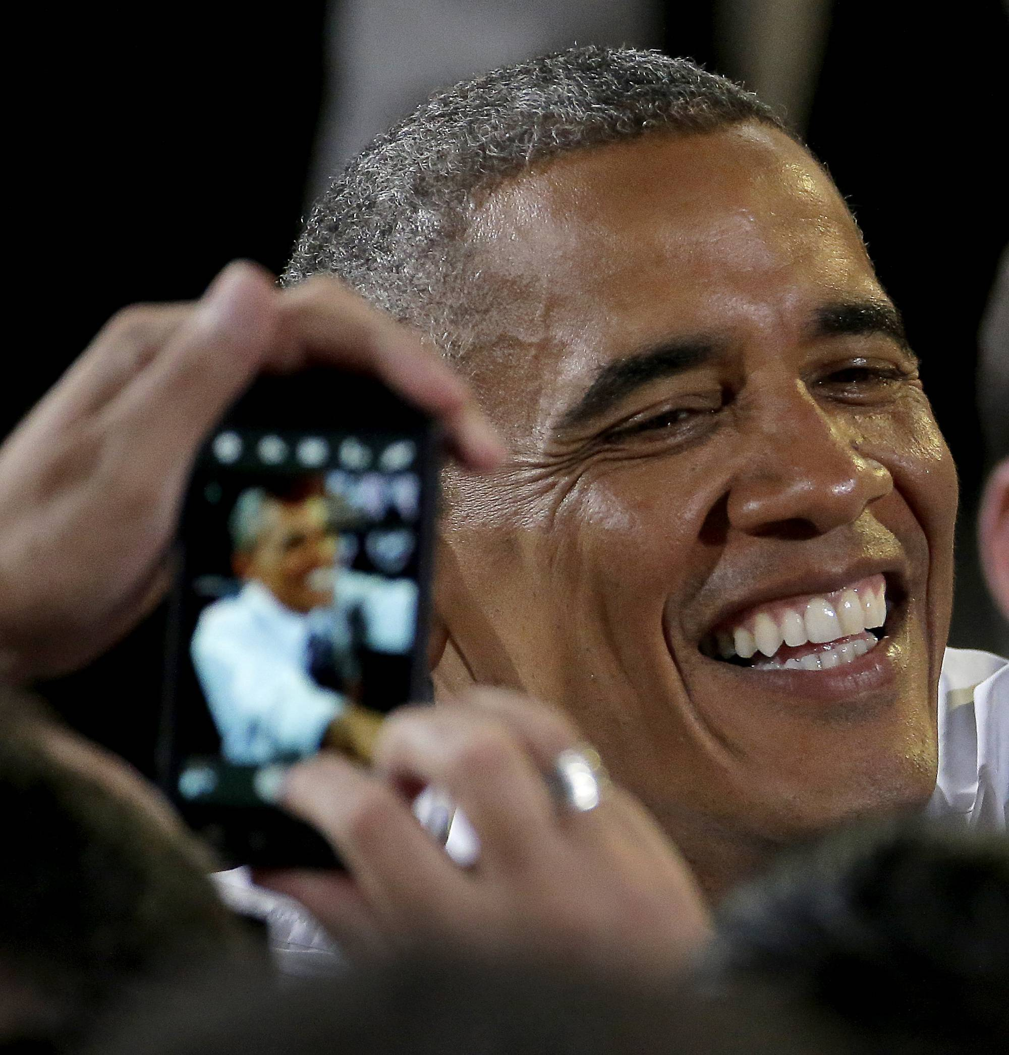 A guest uses a cellphone Wednesday to photograph President Barack Obama as greets the crowd after speaking about the economy at the Uptown Theater in Kansas City, Mo. On Friday, Obama signed a bill into law making it legal once again to unlock a cellphone without permission from your wireless provider.